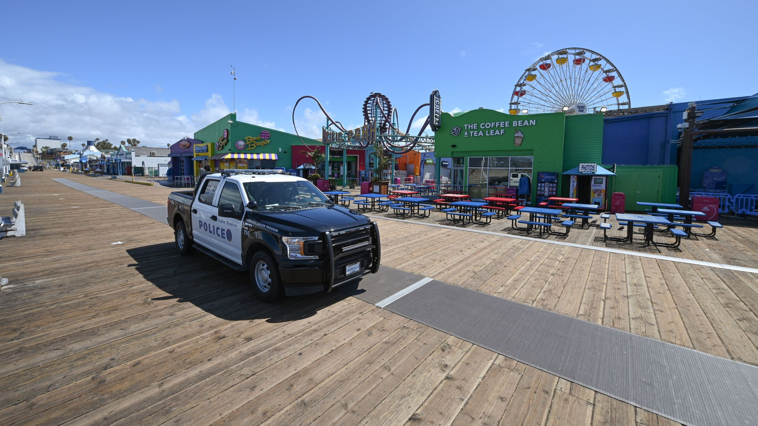Police patrol an empty Santa Monica Pier in Santa Monica, California on March 23, 2020, as people are encouraged to stay at home to halt the spread of the novel coronavirus, COVID-19. (ROBYN BECK/AFP via Getty Images)