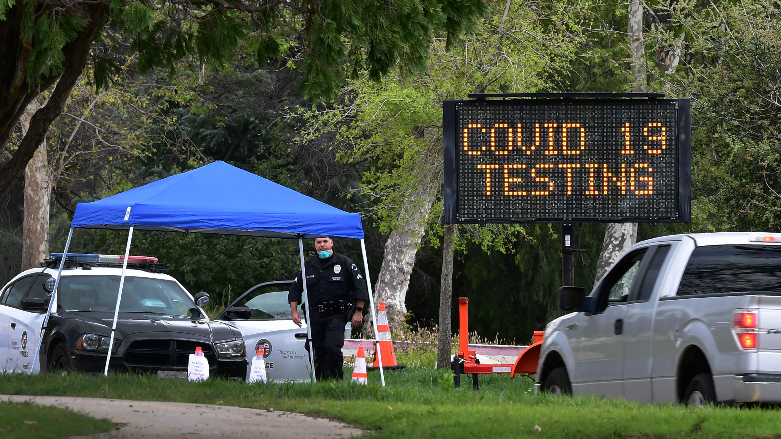 A police officer mans the entrance to a coronavirus (COVID-19) testing center in Hansen Dam Park on March 25, 2020 in Pacoima. (FREDERIC J. BROWN/AFP via Getty Images)
