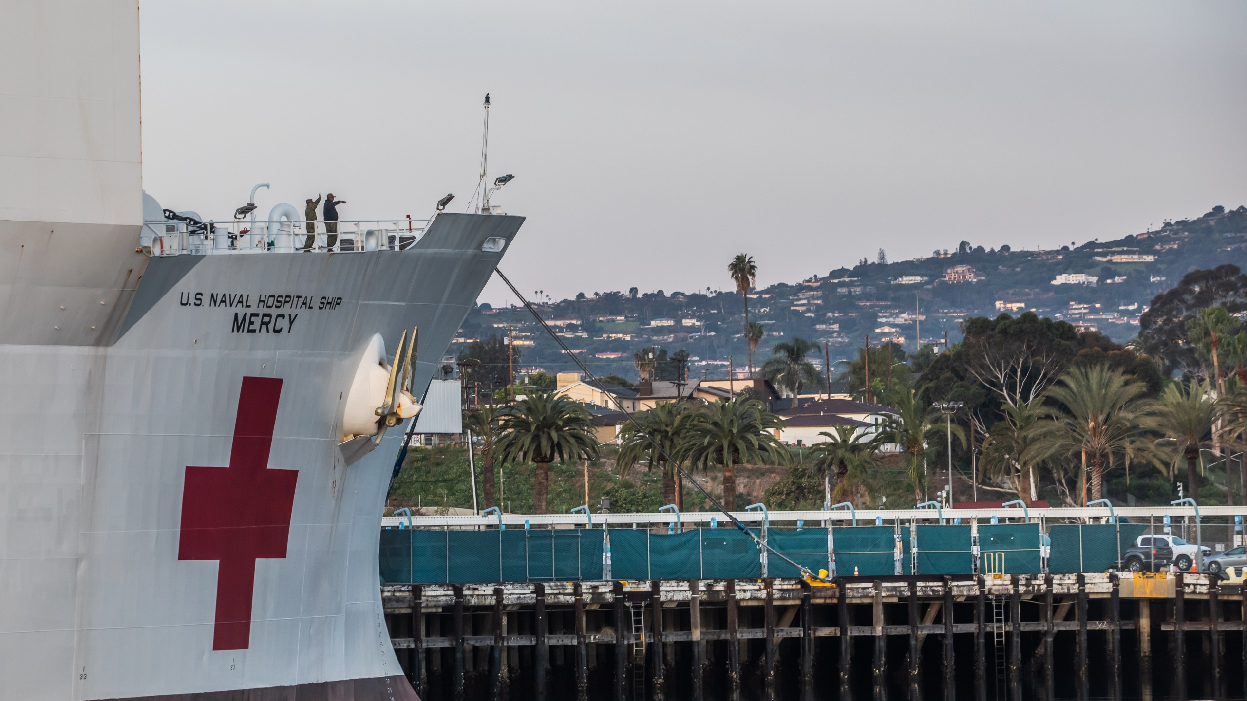 Military personnel of the USNS Mercy wave after the ship docked at the Port of Los Angeles on March 28, 2020. (Credit: Apu Gomes / AFP / Getty Images)