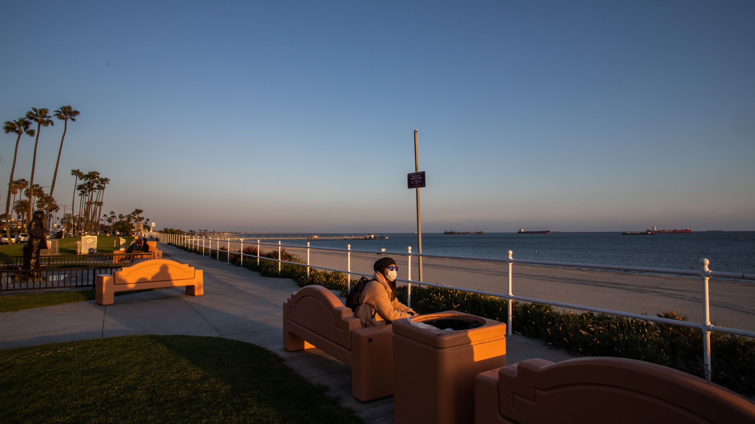 A woman enjoys the sunset while wearing a mask as a preventive measure against the spread of the COVID-19 novel coronavirus in Long Beach, California on March 29, 2020. - President Donald Trump on March 29, 2020, abandoned his timetable for life returning to normal in the United States, extending emergency coronavirus restrictions for another month, while Spain suffered its deadliest day. (Apu Gomes/AFP via Getty Images)