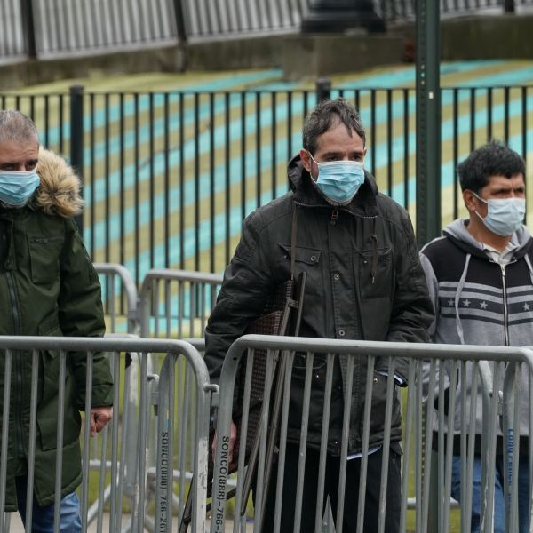 People wearing masks walk past Elmhurst Hospital in the Borough of Queens on March 31, 2020 in New York. (BRYAN R. SMITH/AFP via Getty Images)