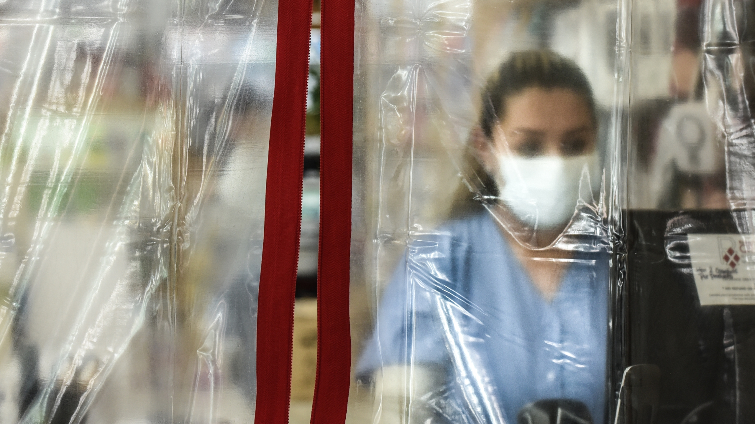 A pharmacist works behind plastic sheeting while wearing personal protective equipment in the Elmhurst neighborhood on April 1, 2020, in New York City. (Stephanie Keith/Getty Images)