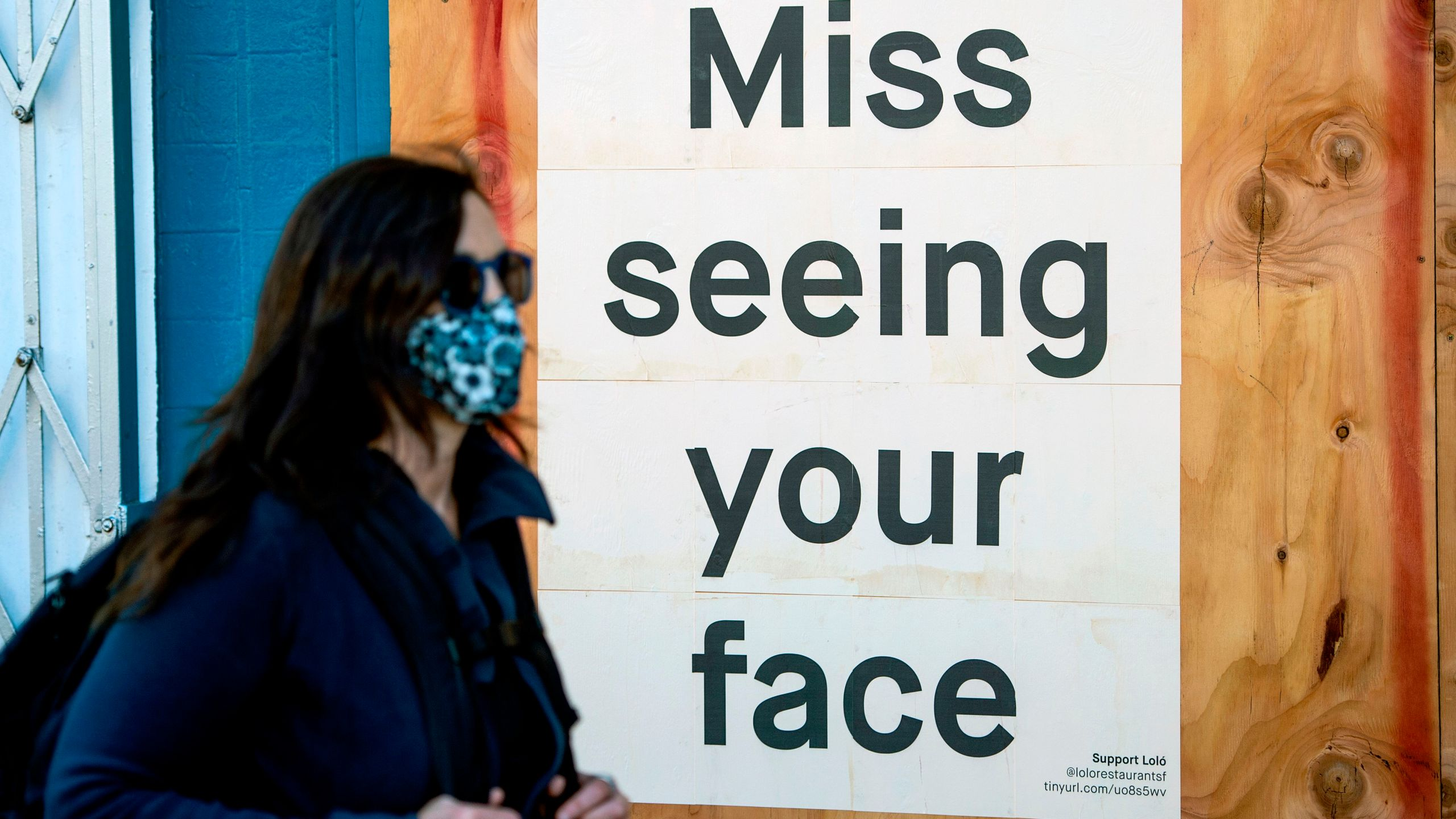 A woman in a face mask walks by a sign posted on a boarded up restaurant in San Francisco on April, 1, 2020. (Josh Edelson/AFP via Getty Images)
