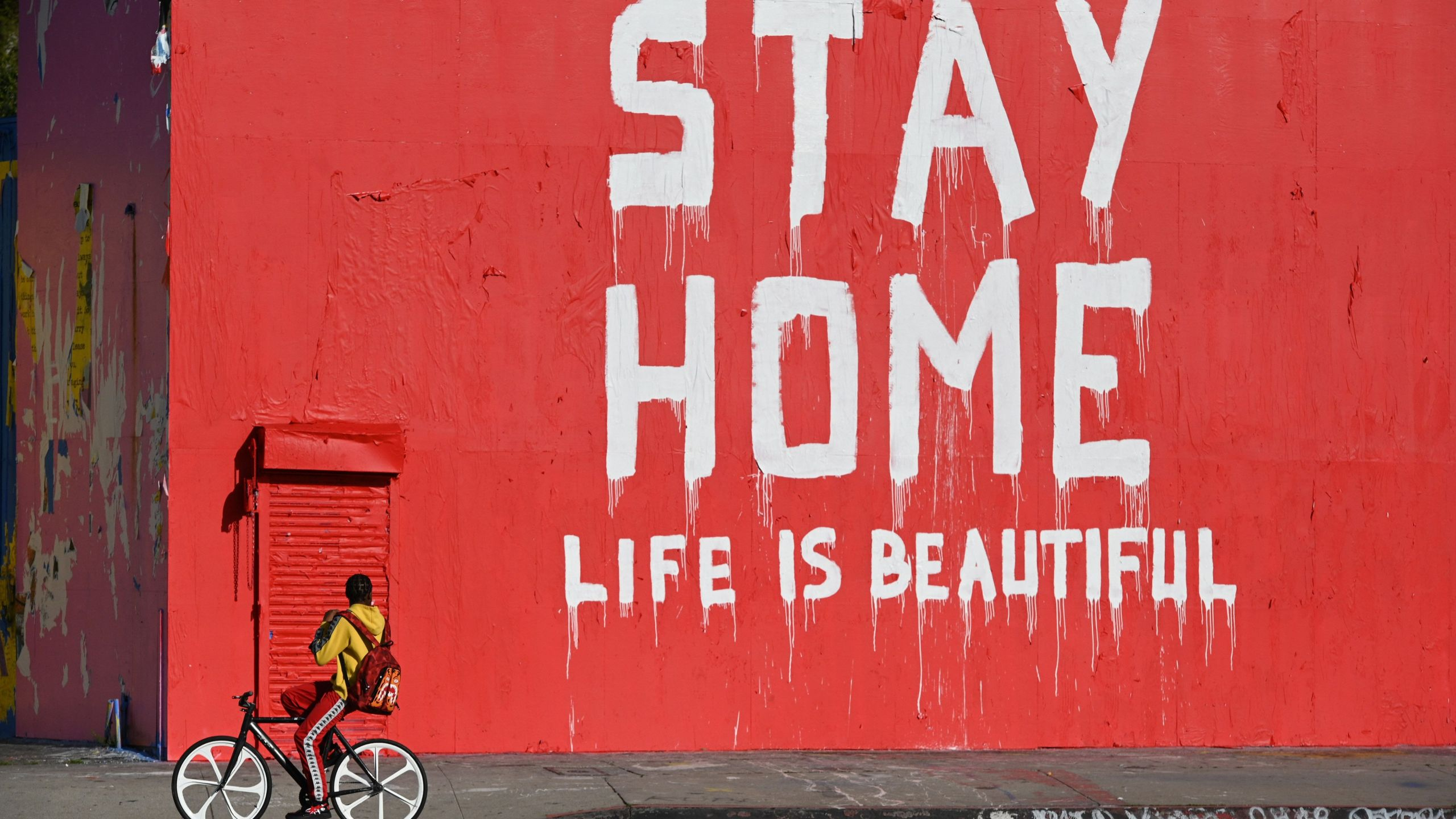 "A person rides a bicycle past a mural reading ""Stay Home / Life Is Beautiful"" during the COVID-19 pandemic on April 3, 2020 in Los Angeles. (ROBYN BECK/AFP via Getty Images)"