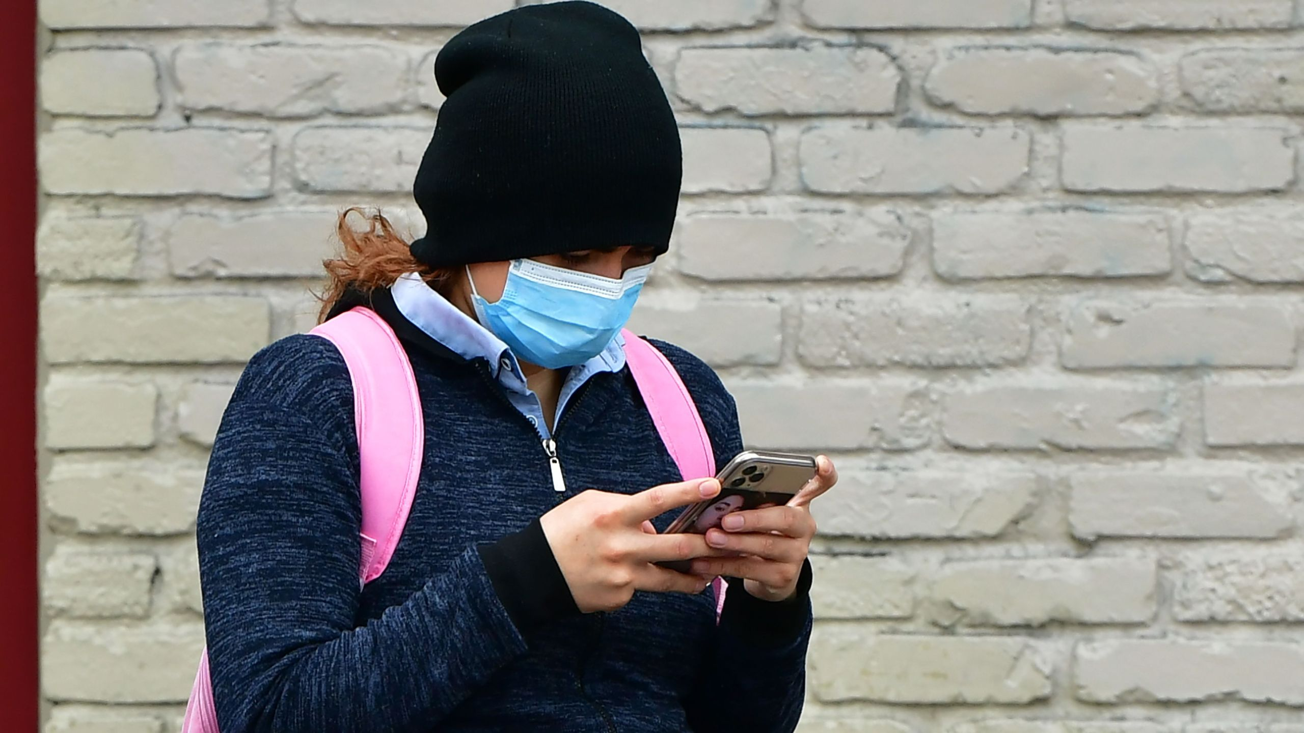 A woman wears a face mask while checking her cellphone in Los Angeles on April 6, 2020. (Credit: Frederic J. Brown / AFP / Getty Images)