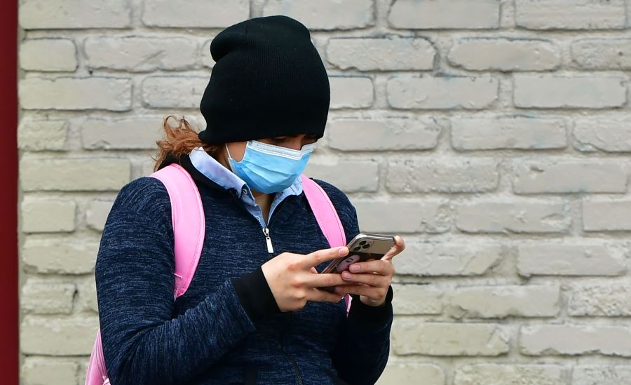 A woman wears a face mask while checking her cellphone in Los Angeles on April 6, 2020. (Frederic J. Brown / AFP / Getty Images)