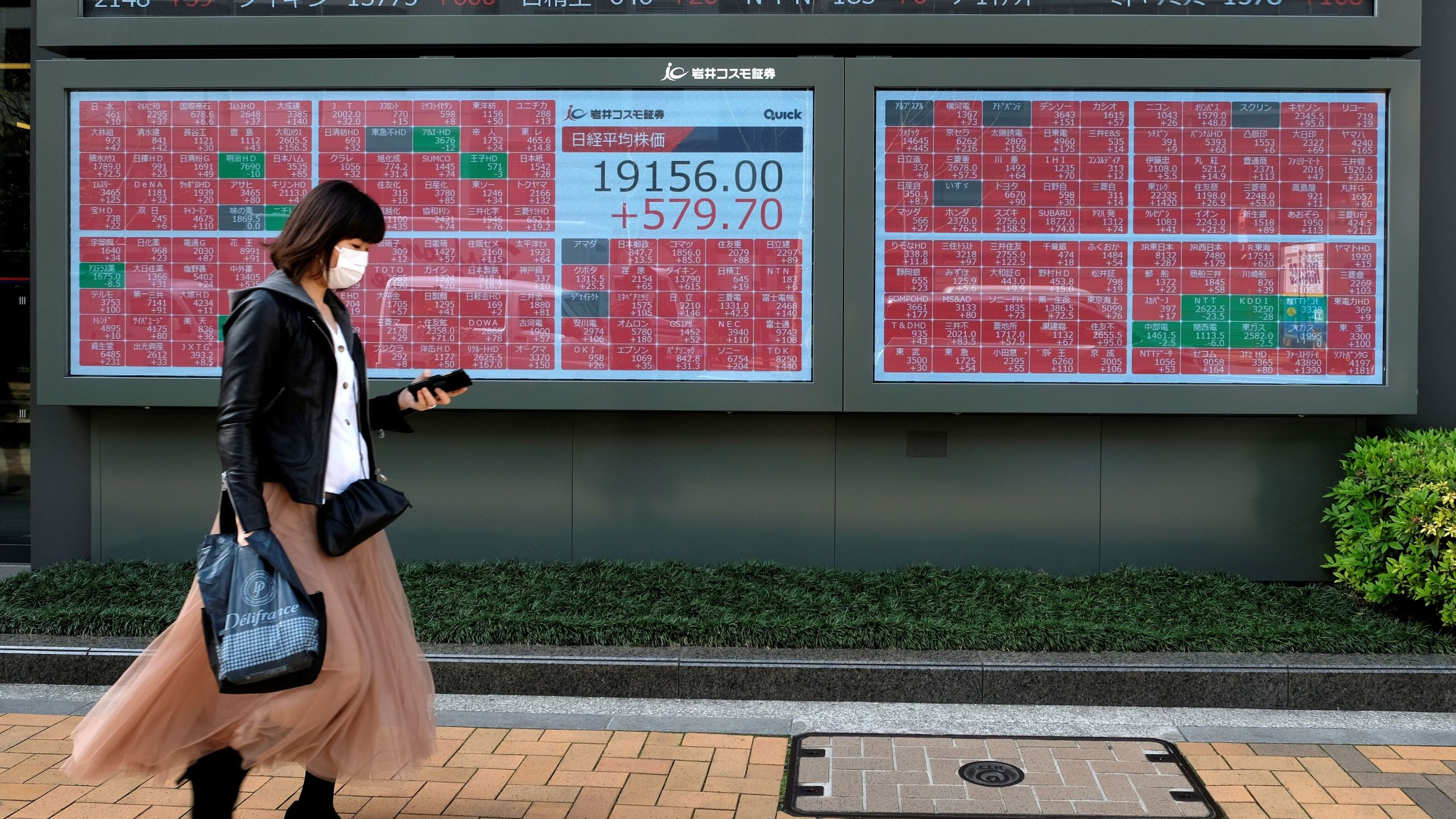 A pedestrian walks past a quotation board displaying share prices of the Tokyo Stock Exchange in Tokyo on April 7, 2020. (KAZUHIRO NOGI/AFP via Getty Images)