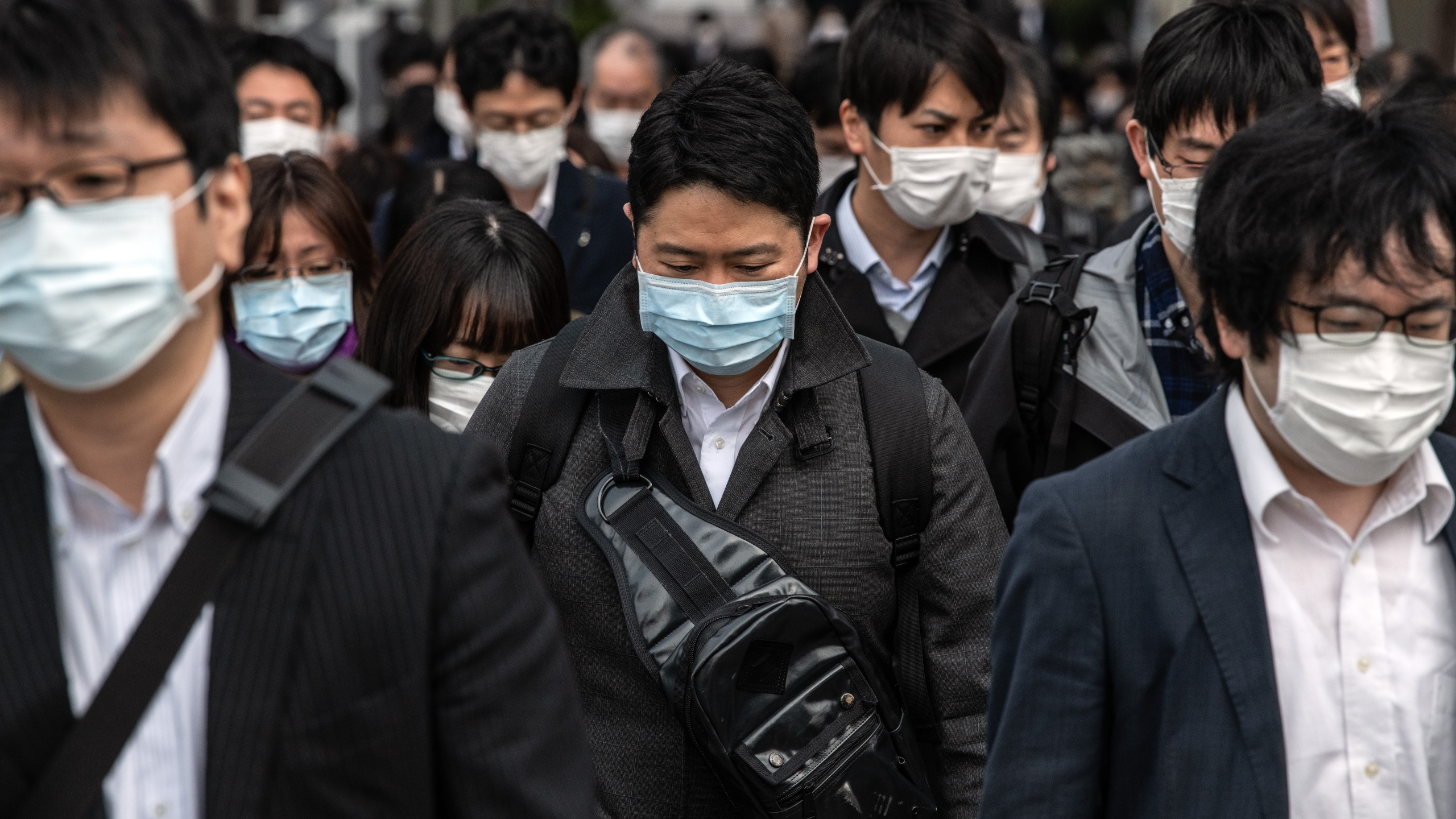 Commuters wearing face masks walk to work the day before a state of emergency is expected to be imposed on April 7, 2020, in Tokyo, Japan. (Carl Court/Getty Images)