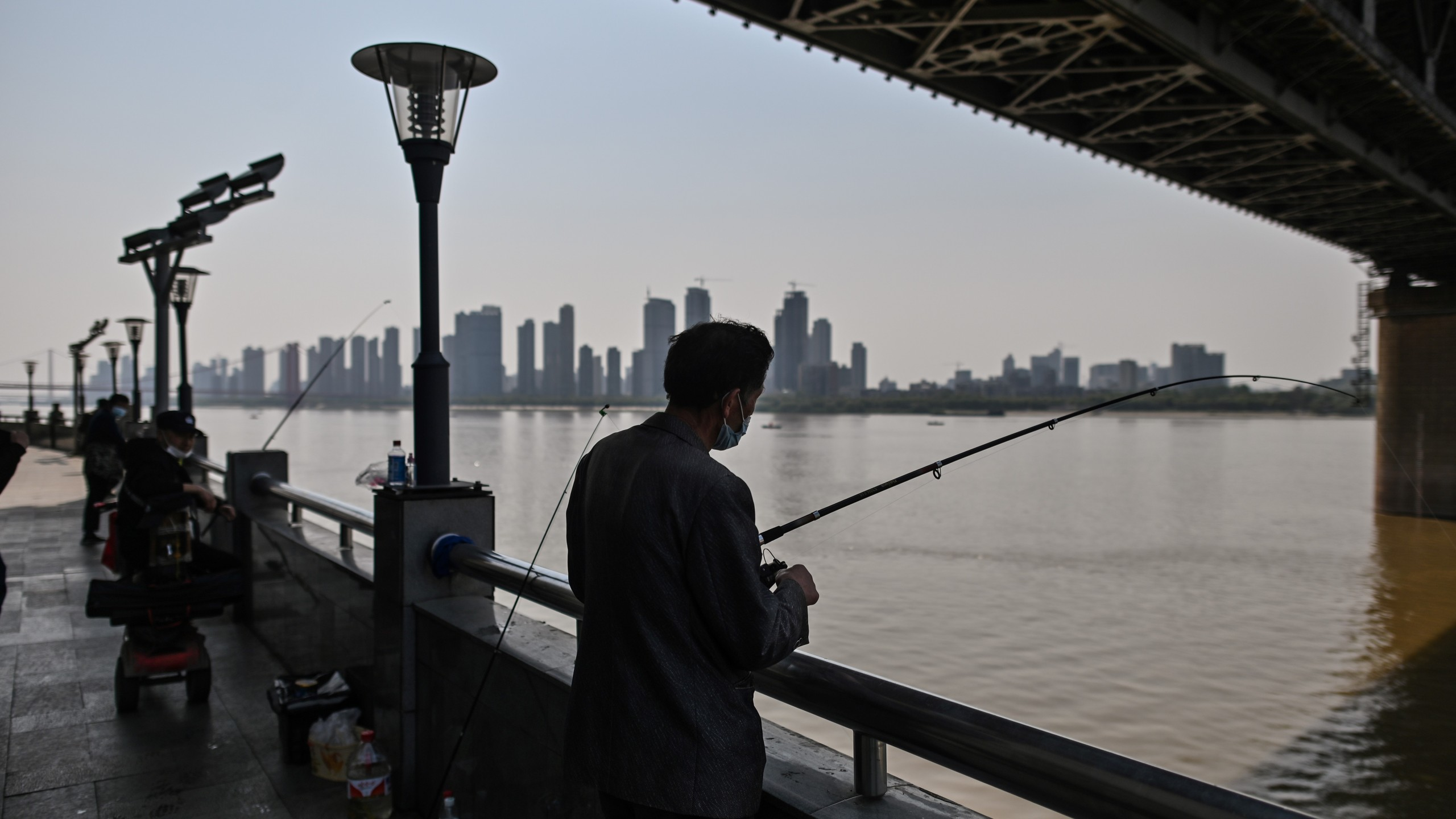 A man wearing a face mask fishes next to Wuhan Bridge in Yangtze River in Wuhan, China, on April 9, 2020. (HECTOR RETAMAL/AFP via Getty Images)