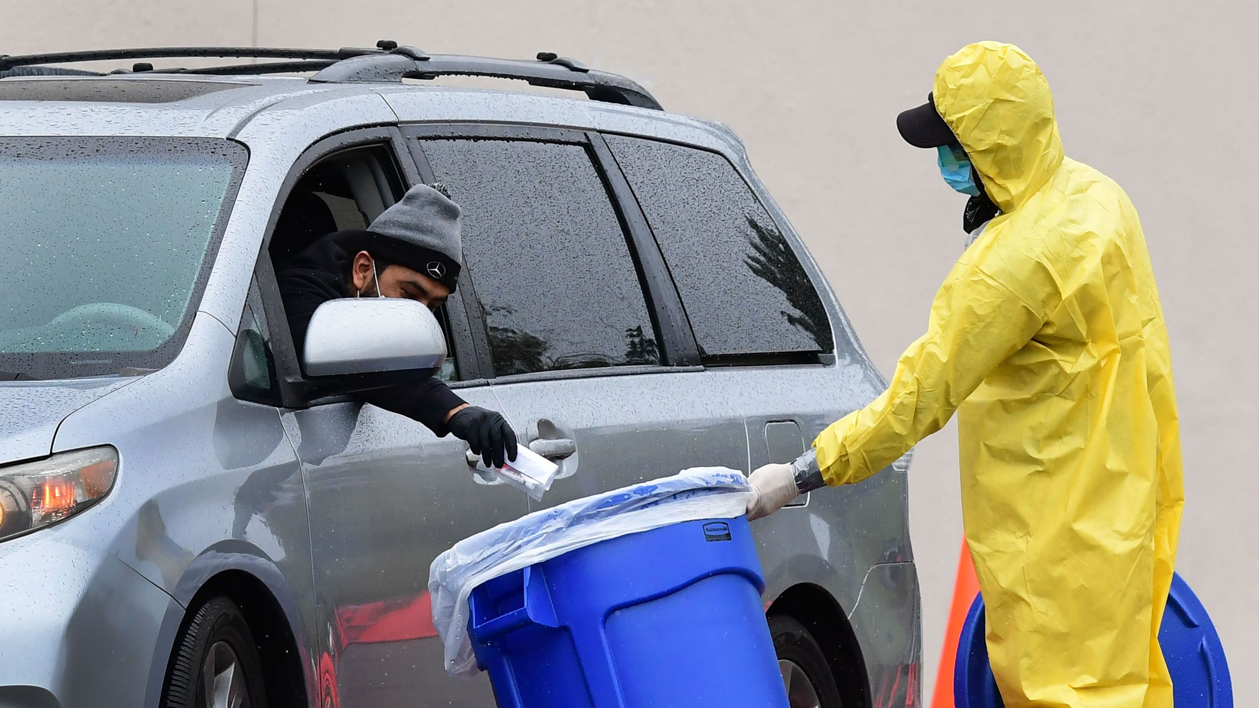 A driver drops his COVID-19 test into a bin at a coronavirus mobile testing site at Lincoln Park in Los Angeles on April 10, 2020. (Credit: Frederic J. Brown / AFP / Getty Images)