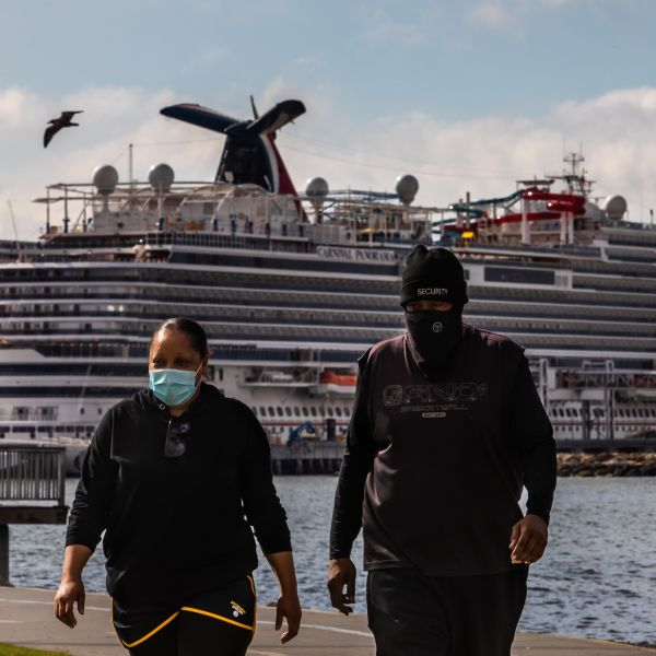 A couple wearing face masks as a preventive measure against the spread of the COVID-19 walk at the Marina Long Beach with Cruise Ships docked at the port due to a no-sail order in Long Beach. (Apu Gomes/AFP via Getty Images)