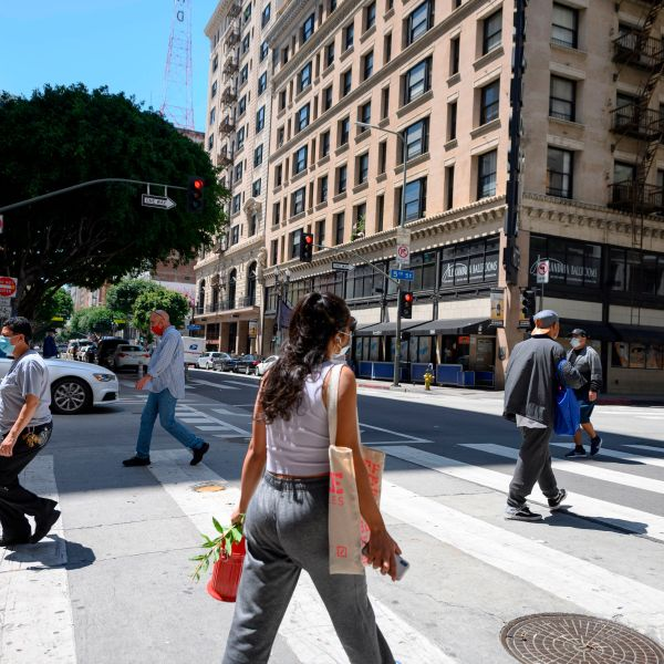 Pedestrians wearing face masks cross an intersection in downtown Los Angeles on April 14, 2020. (ROBYN BECK/AFP via Getty Images)