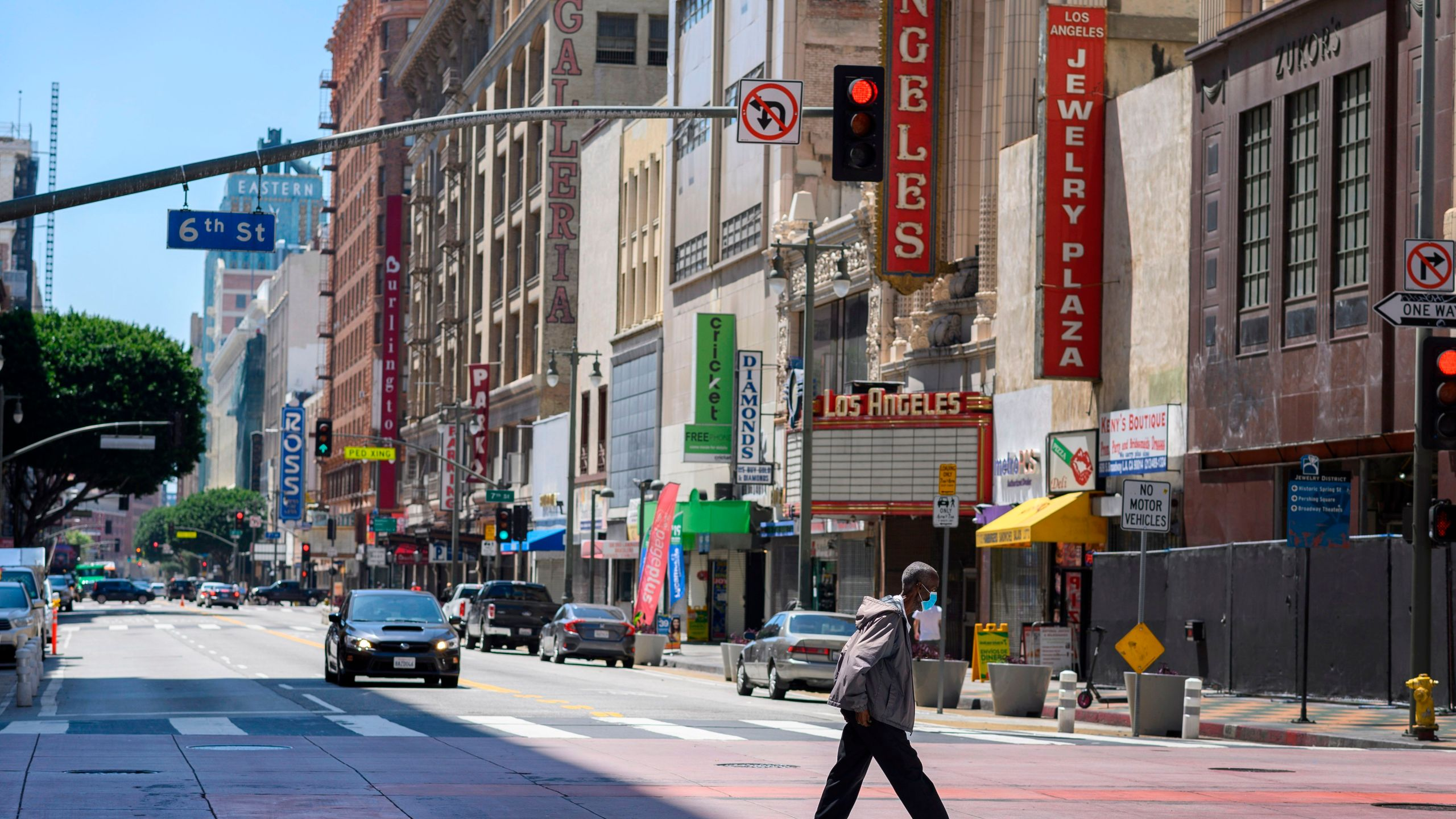 A pedestrian crosses a street in downtown Los Angeles during the coronavirus pandemic on April 14, 2020. (Credit: Robyn Beck / AFP / Getty Images)