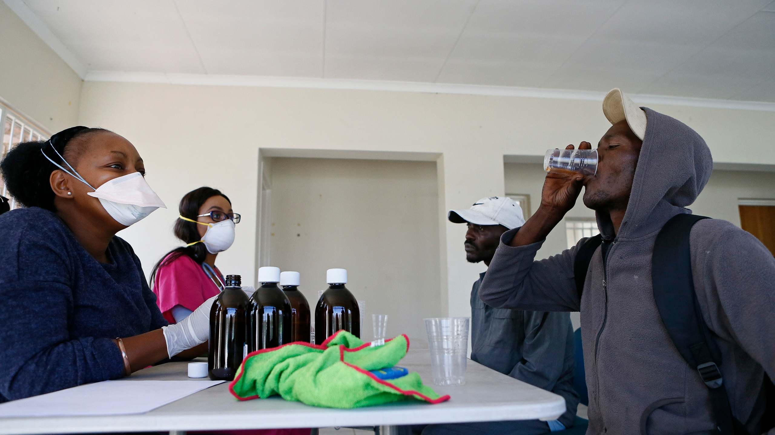 Health professionals look on as a homeless man drinks the Methadone Oral Solution, provided as an effort to care for drug-dependent people, at a shelter at the Lyttelton Sports Centre in Pretoria on April 16, 2020. The building is a temporary shelter being provided for homeless people amid the COVID-19 pandemic in South Africa. (Phill Magakoe / AFP via Getty Images)