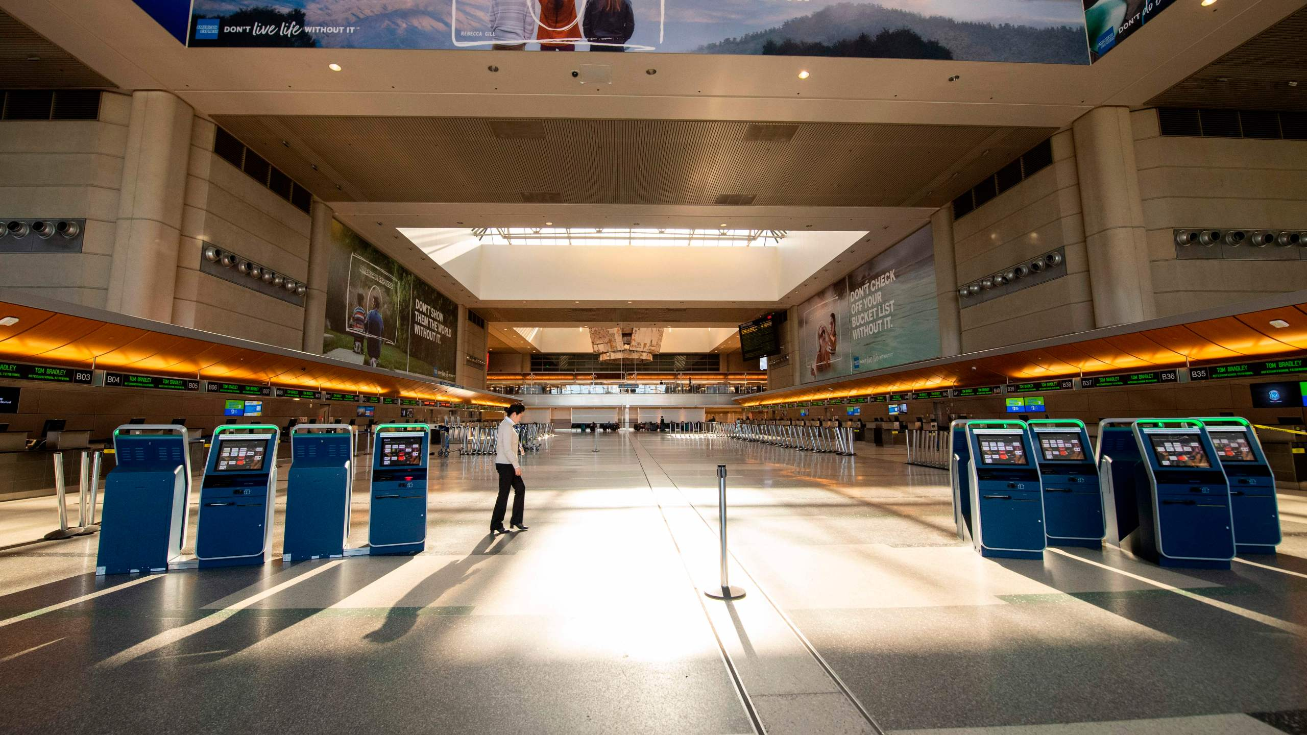 A woman walks through an empty Tom Bradley Terminal at Los Angeles International Airport on April 16, 2020, in Los Angeles. (VALERIE MACON/AFP via Getty Images)