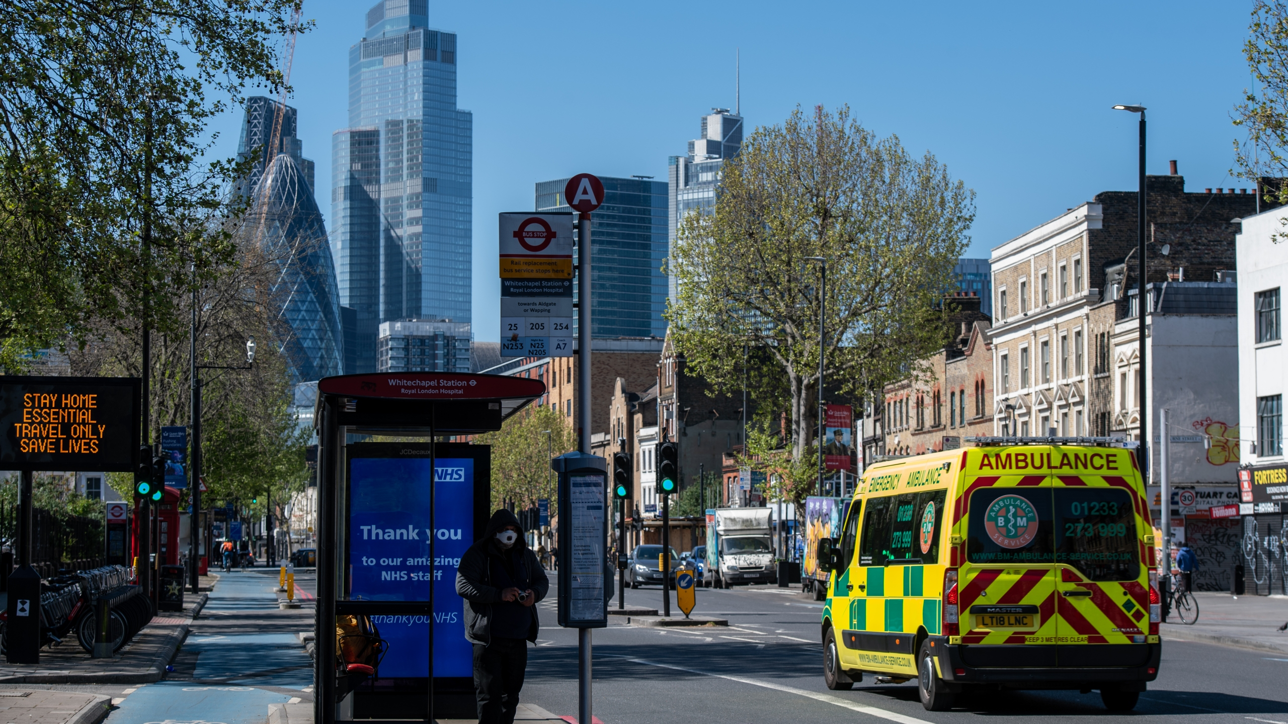 Skyscrapers are seen in the distance as a man wearing a face mask waits at a bus stop outside Royal London Hospital on April 19, 2020. (Chris J. Ratcliffe/Getty Images)