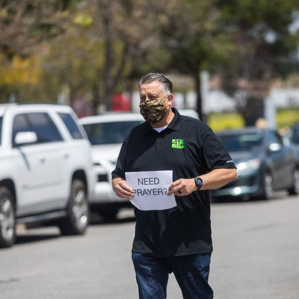 Simon Cooper offers prayers to people who attended an on line Sunday Service inside their cars at the Christian '412 Church Murrieta' parking lot on April 19, 2020. (Apu GOMES / AFP via Getty Images)
