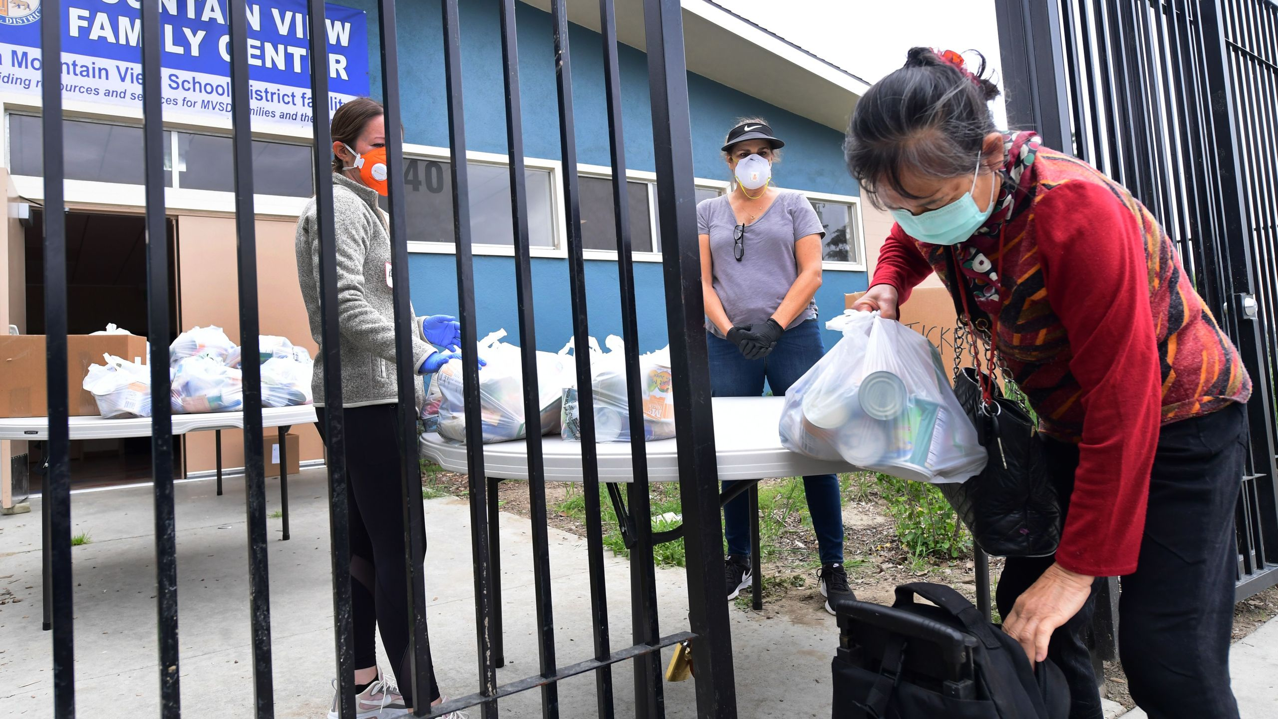 Volunteers in masks and gloves watch as a woman loads her bag of groceries at a food bank opened in response to the coronavirus pandemic on April 20, 2020 in El Monte. (Frederic J. BROWN / AFP/Getty Images)