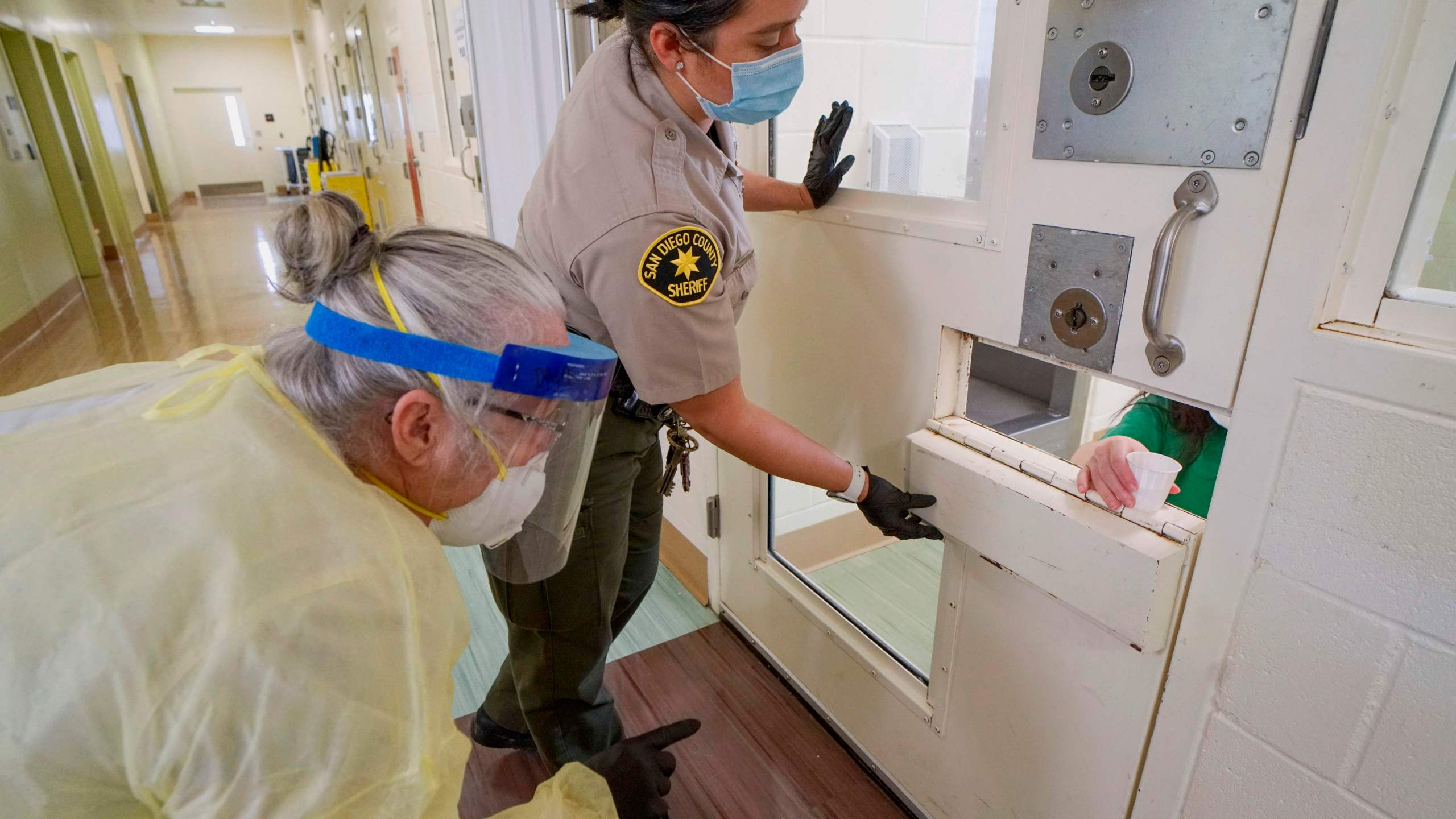 A Sheriff's deputy and an on-site nurse give medications to an inmate at Las Colinas Women's Detention Facility in Santee, California, on April 22, 2020. (Sandy Huffaker/ AFP via Getty Images)