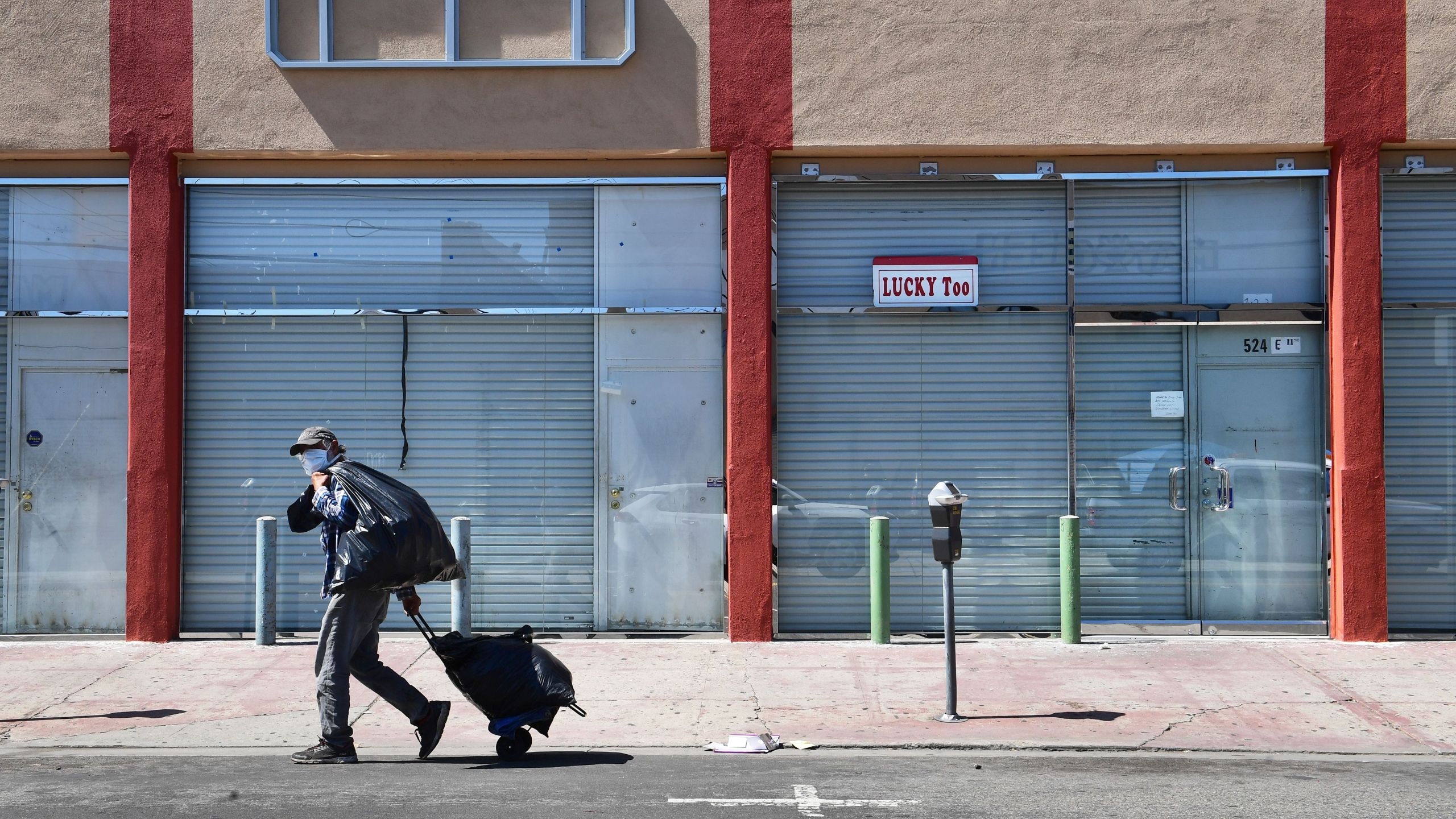 A man in a face mask walks past closed shopfronts in the Fashion District in Downtown Los Angeles, California on April 22, 2020, amid the novel coronavirus pandemic. (FREDERIC J. BROWN/AFP via Getty Images)