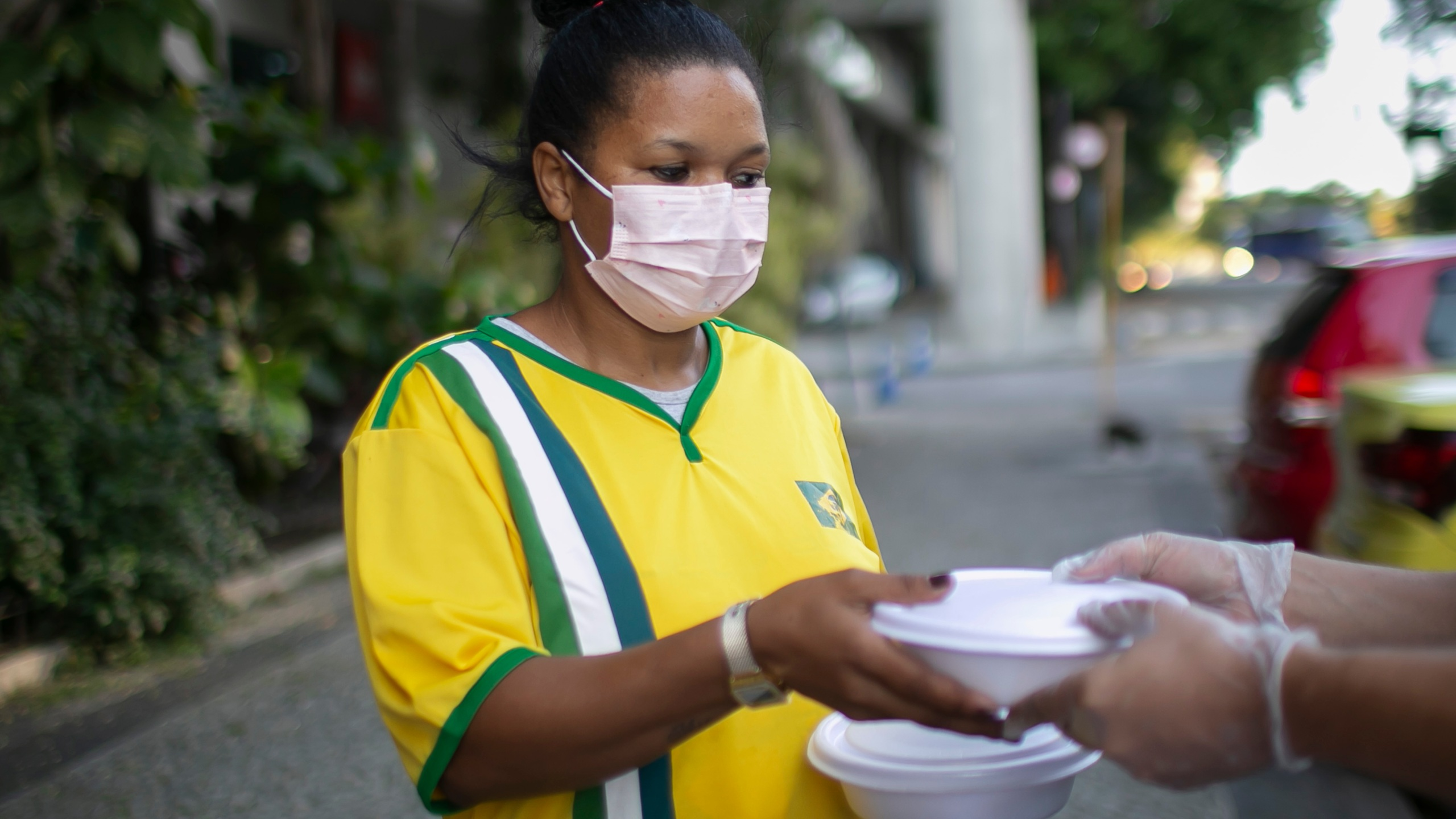 A homeless and unemployed person receives food and water from volunteers of the 'Covid Sem Fome' on April 22, 2020 in Rio de Janeiro, Brazil. (Bruna Prado/Getty Images)