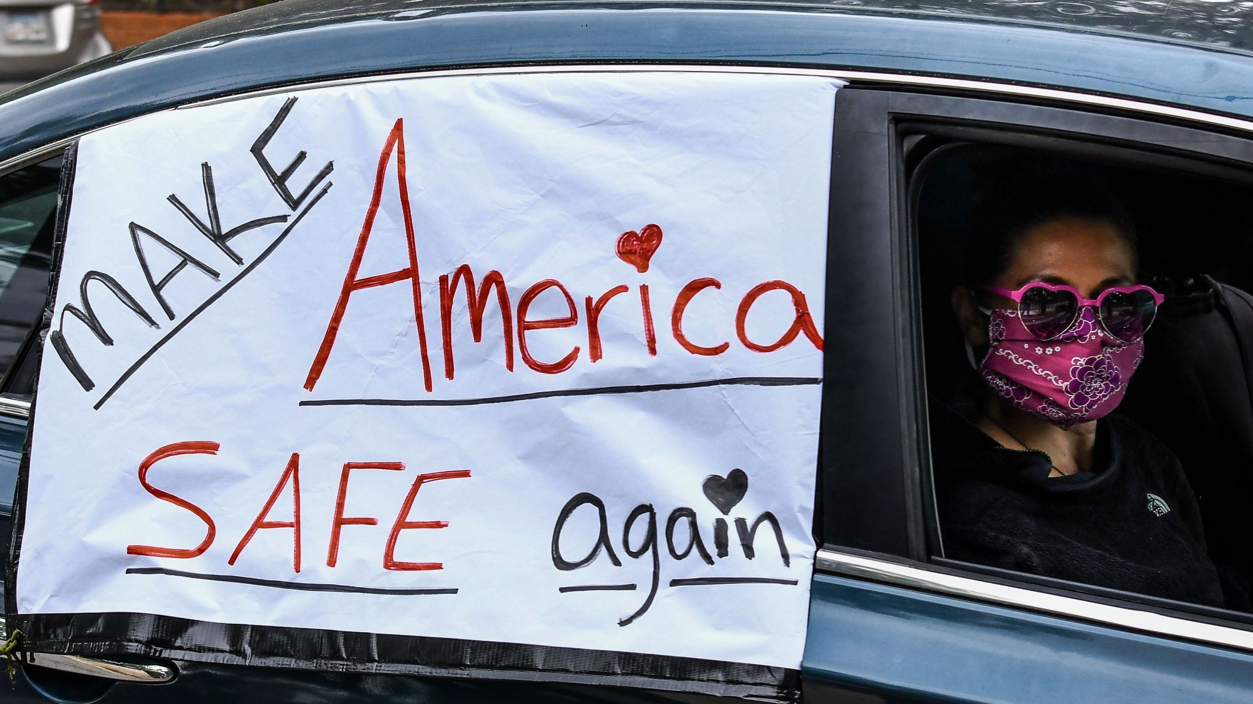 "A demonstrator shows a sign with ""Make America safe again"" written on it while driving past the Governor's Mansion during a drive by protest in Atlanta, Georgia on April 24, 2020. (CHANDAN KHANNA/AFP via Getty Images)"