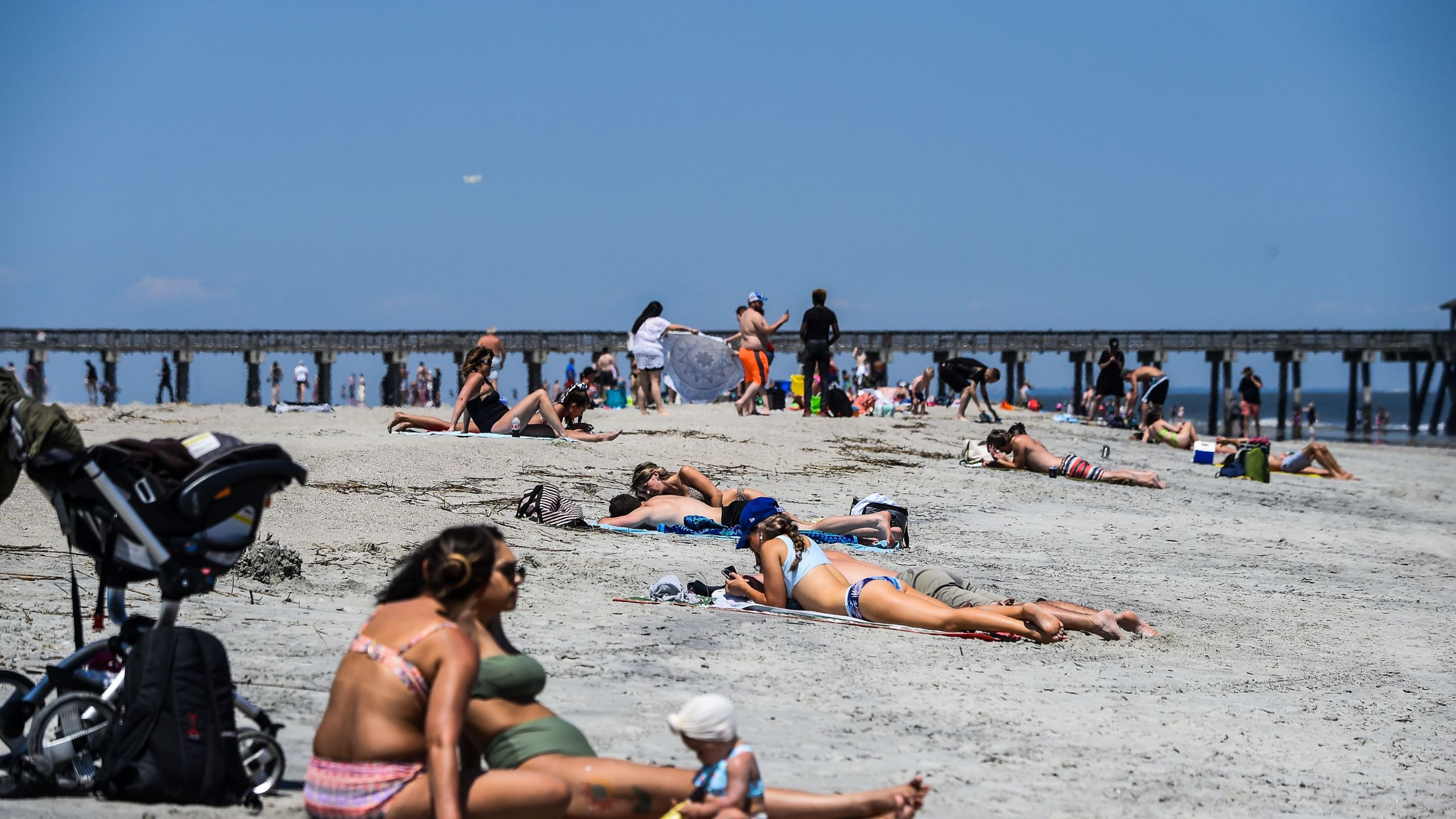People relax on the Tybee Beach in Tybee Island, Georgia on April 25, 2020. The Tybee Island city council voted to close the beaches on March 20, but Georgia Gov. Brian Kemp issued a statewide shelter-in-place executive order which supersedes all local orders relating to coronavirus and also opened up the state's beaches. (CHANDAN KHANNA/AFP via Getty Images)