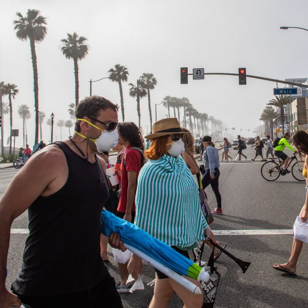 People cross the street, some wearing masks, in Huntington Beach amid the novel coronavirus pandemic on April 25, 2020. (Apu Gomes / AFP / Getty Images)
