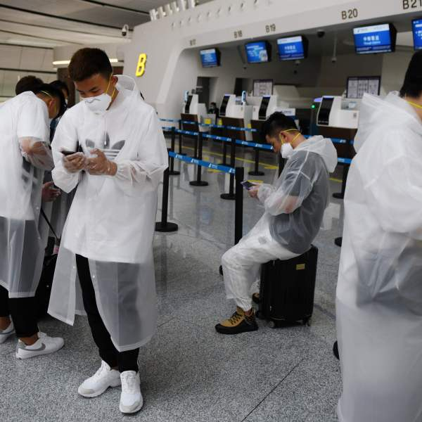 People wear protective clothing amid concerns of the COVID-19 coronavirus as they wait at a check-in counter at Beijing Daxing Airport on the eve of a five-day national holiday on April 30, 2020.(GREG BAKER/AFP via Getty Images)