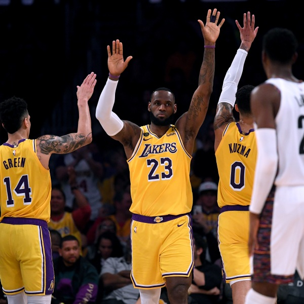 LeBron James of the Los Angeles Lakers celebrates his basket and a Brooklyn Nets foul with Danny Green and Kyle Kuzma at Staples Center on March 10, 2020. (Credit: Harry How / Getty Images)