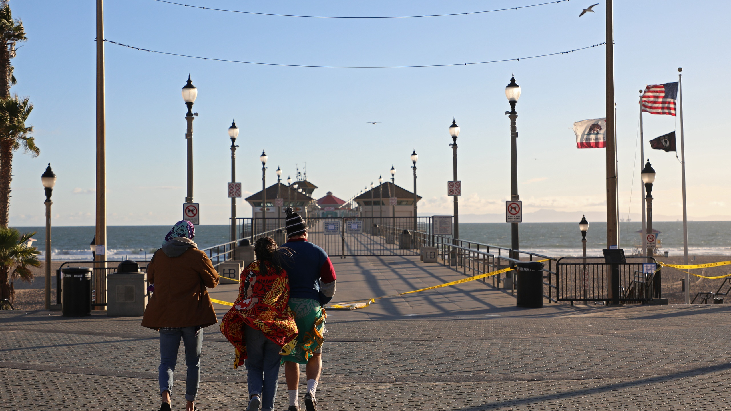 "People stand in front of the closed Huntington Beach Pier on March 24, 2020, in Huntington Beach. Gov. Gavin Newsom at the time issued a ""soft closure"" of state parks in the hopes of slowing the spread of COVID-19. (Michael Heiman/Getty Images)"