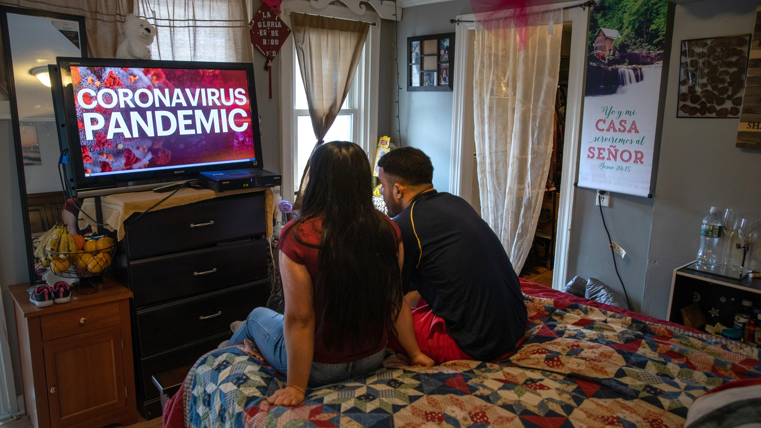 Undocumented immigrant Juana, 24, from El Salvador, and her husband Saul, 23, from Honduras, watch local news in their one-room apartment in Norwalk, Connecticut, on March 25, 2020. (Credit: John Moore / Getty Images)