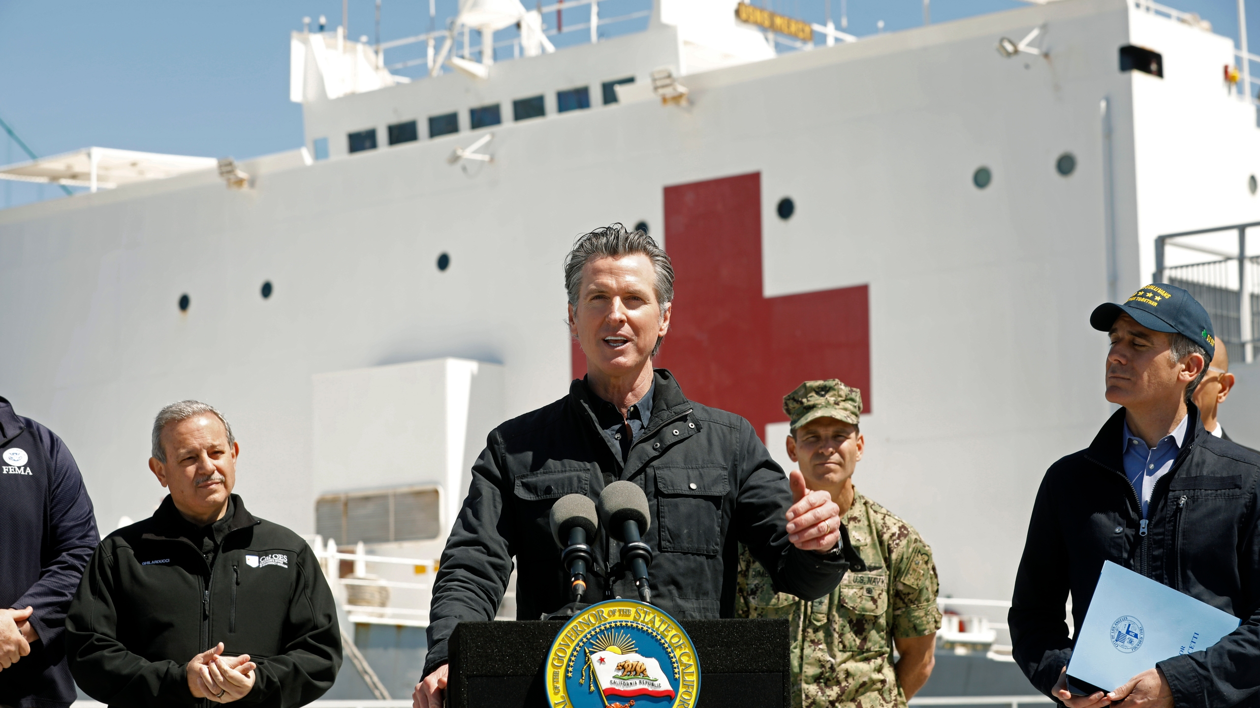 Gov. Gavin Newsom speaks in front of the hospital ship USNS Mercy after it arrived into the Port of Los Angeles on March 27, 2020. (Credit: Carolyn Cole / Getty Images)