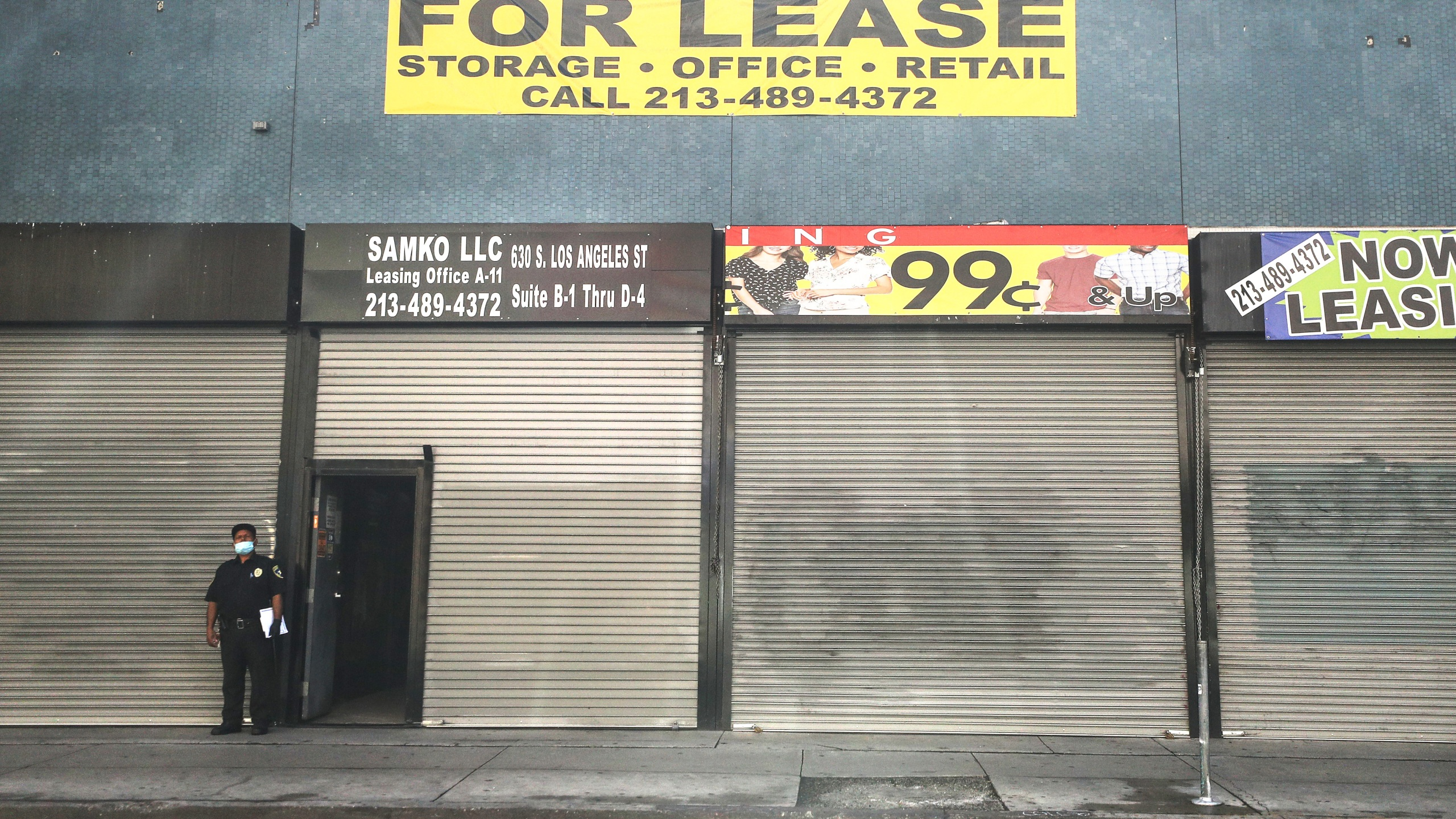 A security guard wears a face mask while standing outside shuttered shops and a 'For Lease' sign amid the global coronavirus pandemic on March 30, 2020 in Los Angeles, California. (Mario Tama/Getty Images)