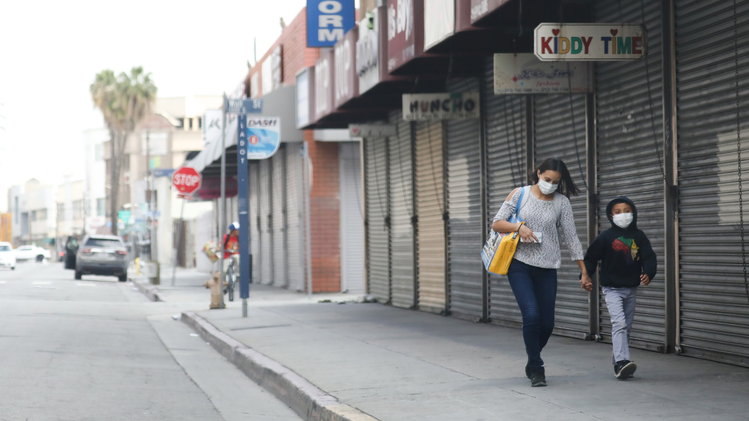 A woman and child wear face masks while walking past shuttered downtown L.A. shops amid the coronavirus pandemic on April 4, 2020. (Mario Tama/Getty Images)
