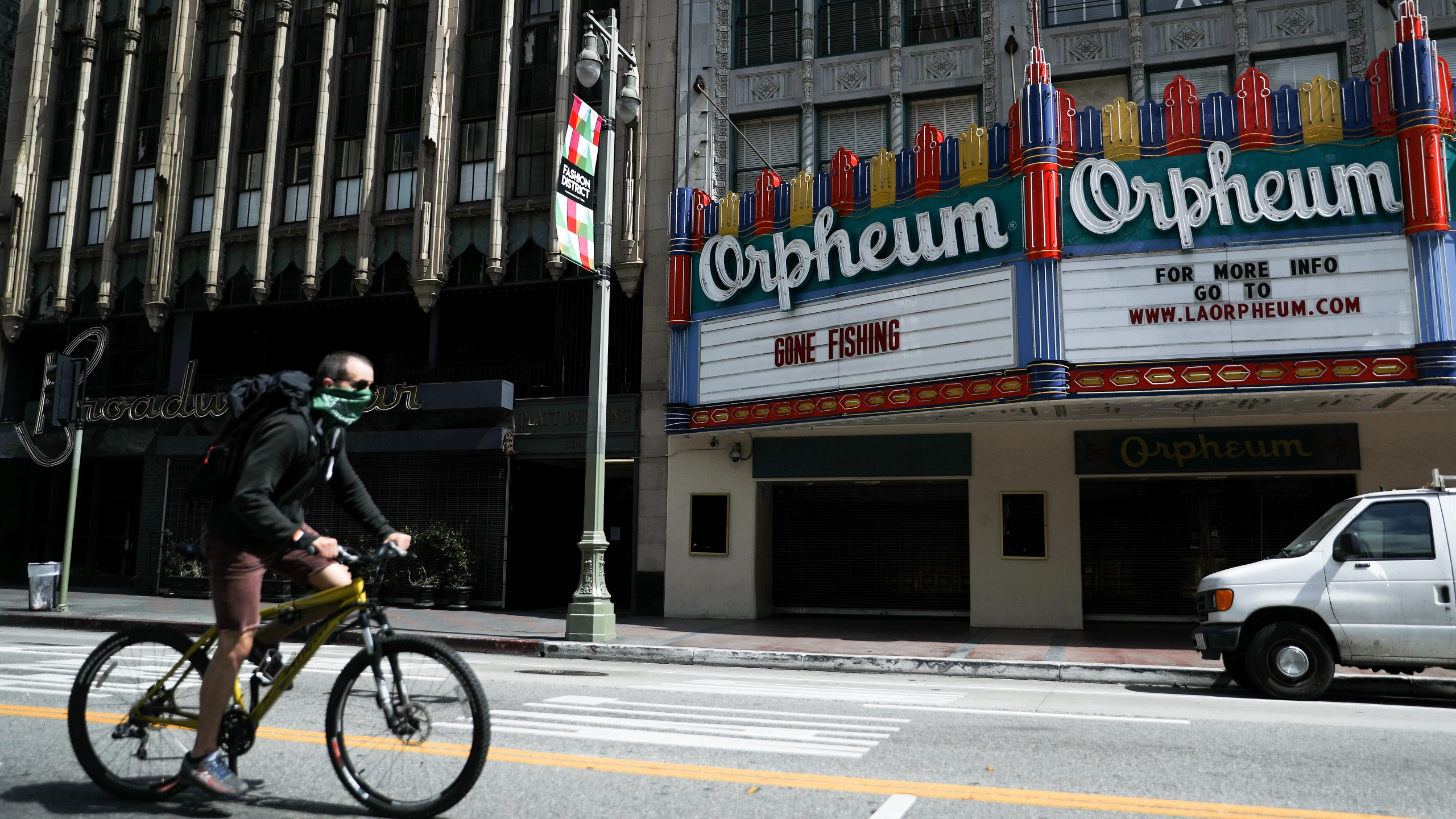 "A man wears a face covering while biking past a shuttered theater with the phrase ""Gone Fishing"" written on the marquee amid the coronavirus pandemic on April 4, 2020 in Los Angeles. (Mario Tama/Getty Images)"