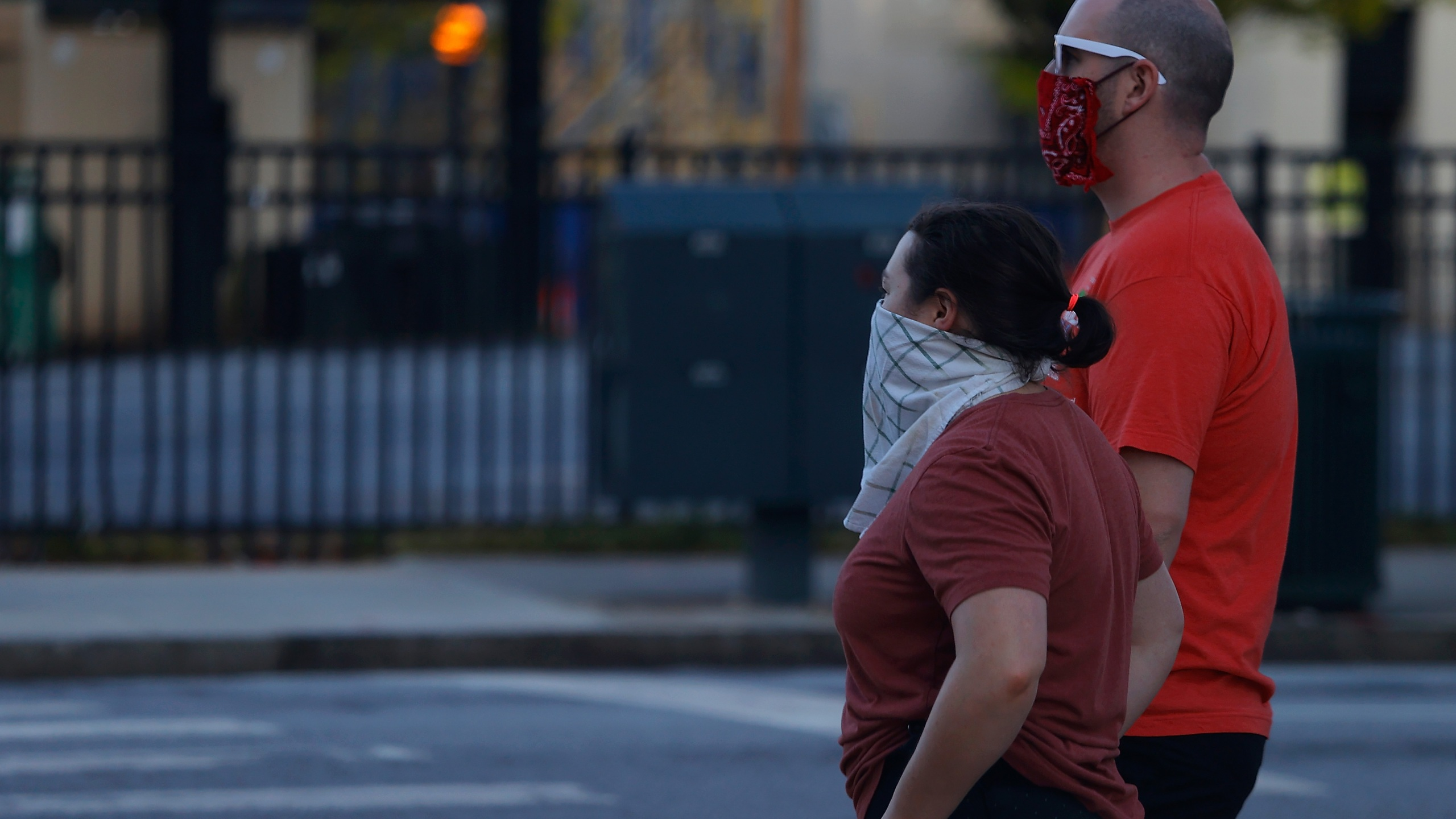 Two pedestrians wearing bandanas over their faces wait to cross Centennial Olympic Park Drive NW on April 4, 2020 in Atlanta, Georgia. (Kevin C. Cox/Getty Images)