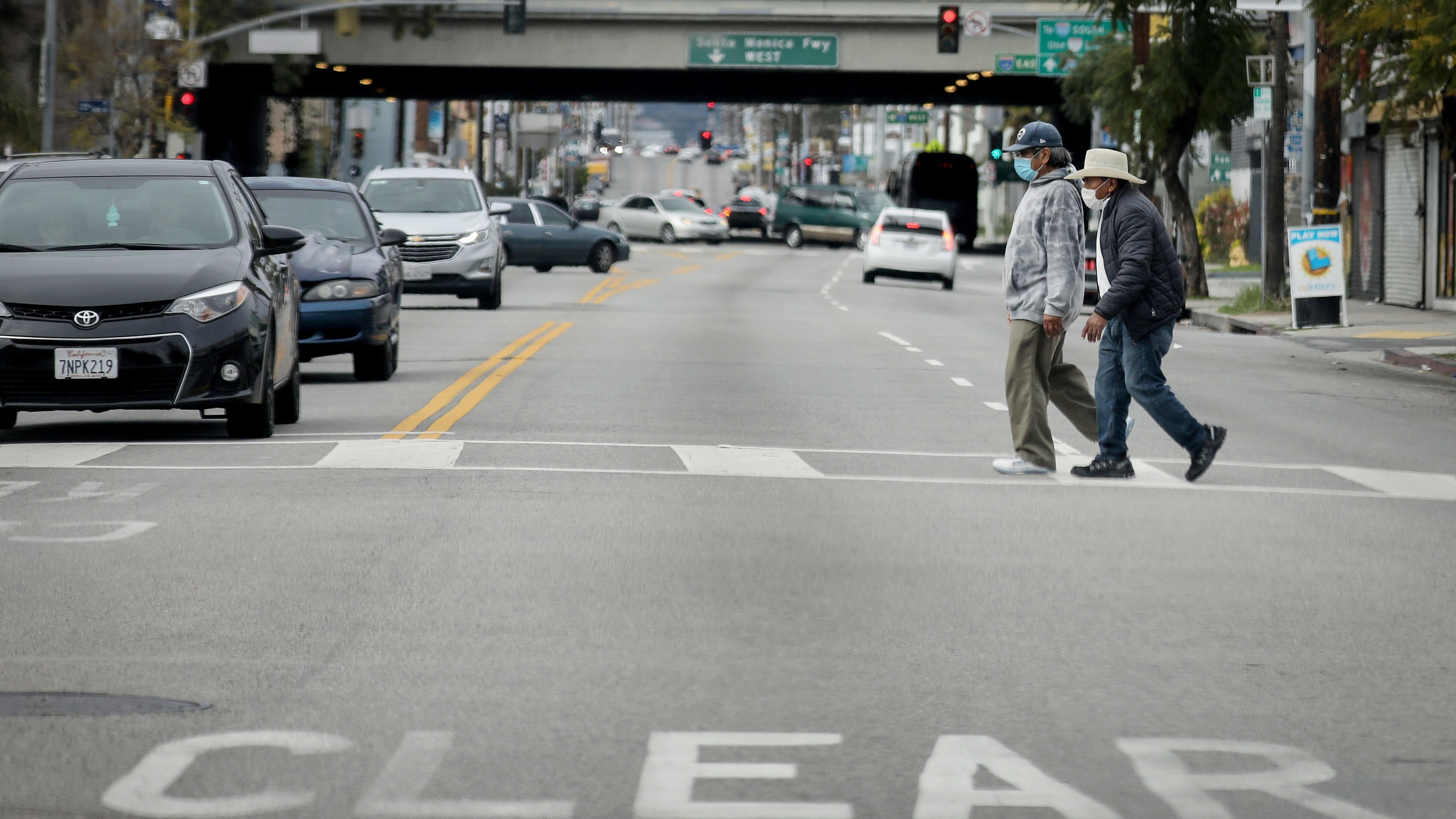 Men cross a street wearing face masks amid the coronavirus pandemic in Los Angeles on April 6, 2020. (Mario Tama/Getty Images)