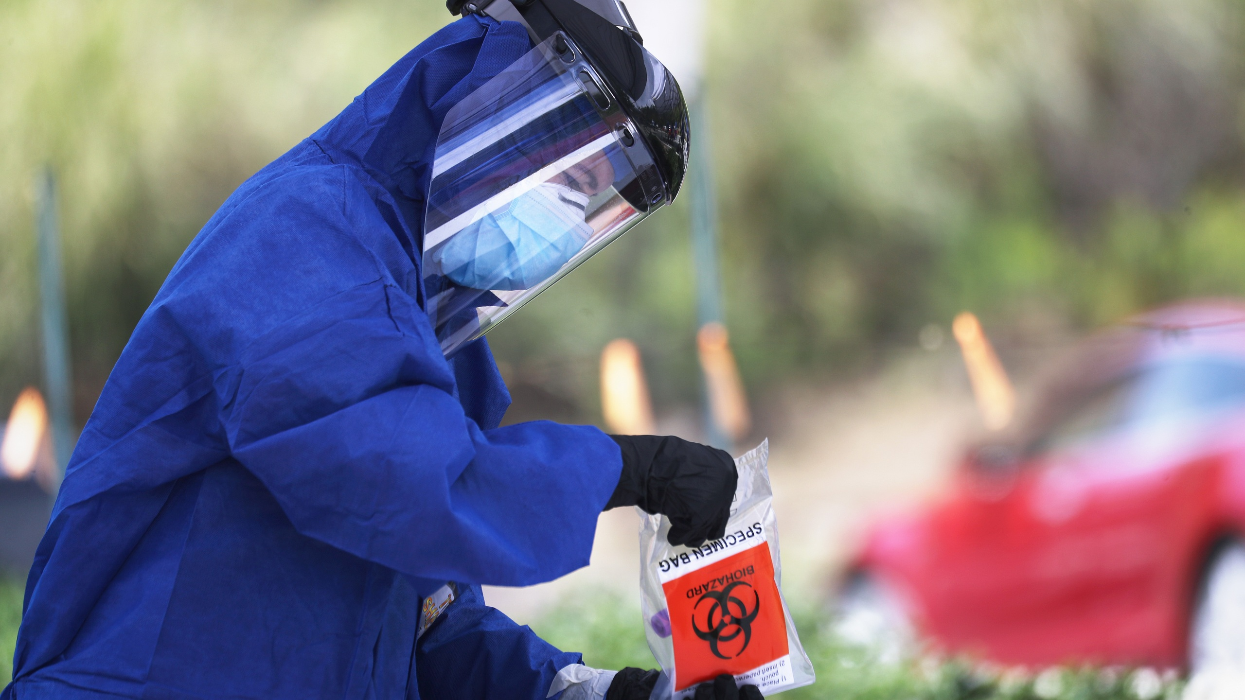 A volunteer holds a specimen bag at a drive-through coronavirus testing site outside Malibu City Hall on April 8, 2020. (Mario Tama/Getty Images)