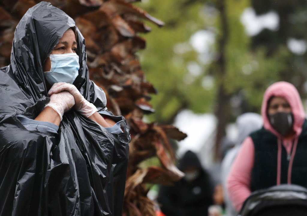 Juana Gomez, 50, from North Hollywood, wears a face mask and gloves, while using a trash bag to protect against the rain, as she waits in line to receive food at a Food Bank distribution for those in need as the coronavirus pandemic continues on April 9, 2020, in Van Nuys, California. (Mario Tama/Getty Images)