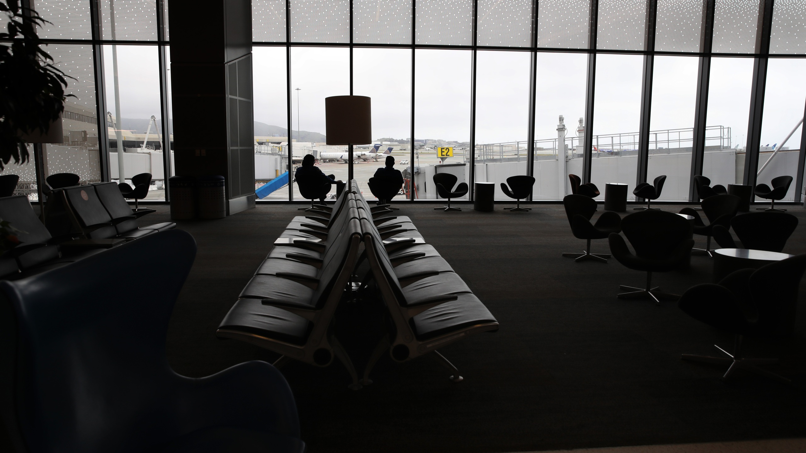 Two worker sit in an empty United Airlines terminal at San Francisco International Airport on April 12, 2020, in San Francisco. (Justin Sullivan/Getty Images)