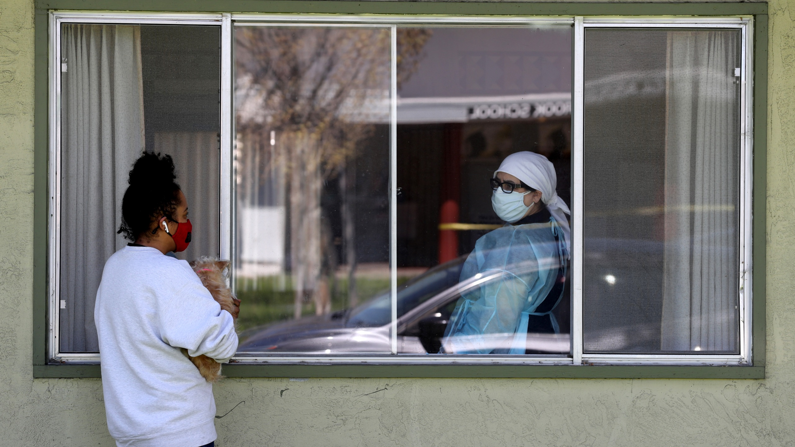Adrina Rodriguez (L) talks with a nurse through a window as she visits her father who is a patient at the Gateway Care and Rehabilitation Center that has tested negative for COVID-19 on April 14, 2020, in Hayward, California. (Justin Sullivan/Getty Images)