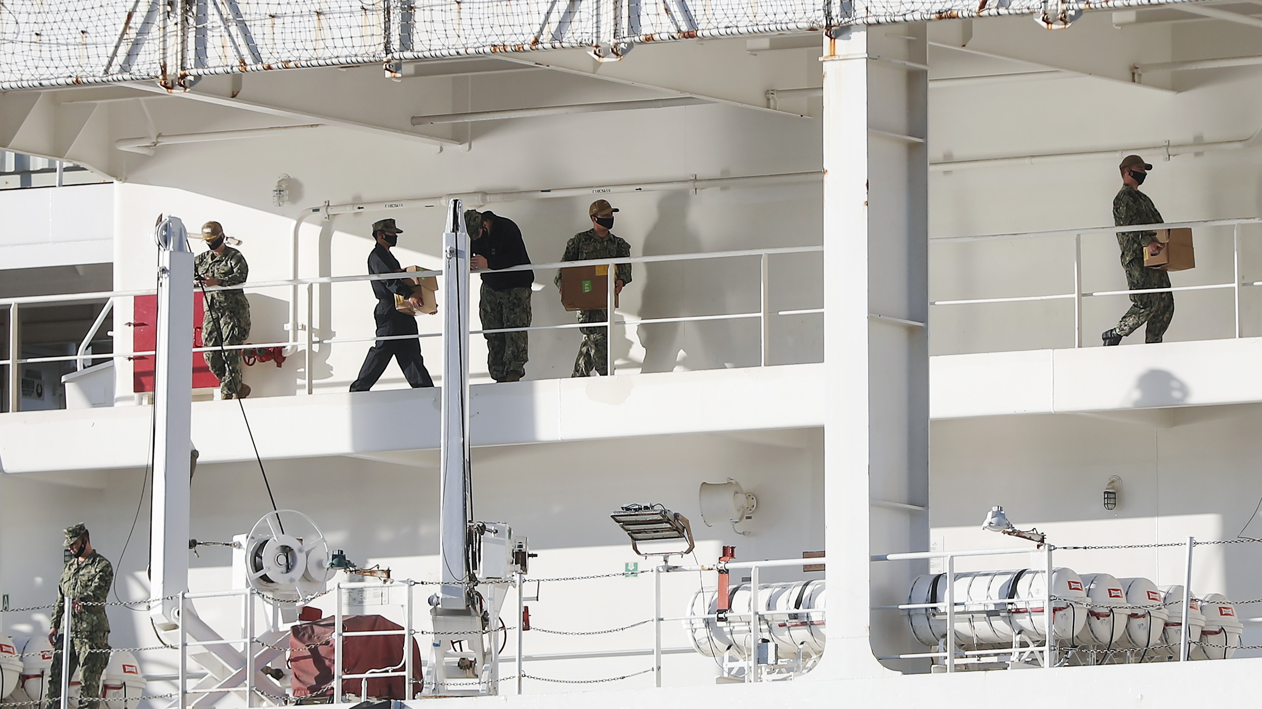 Military personnel wearing face masks work aboard the USNS Mercy hospital ship docked in the Port of Los Angeles amidst the coronavirus pandemic on April 15, 2020. (Credit: Mario Tama / Getty Images)
