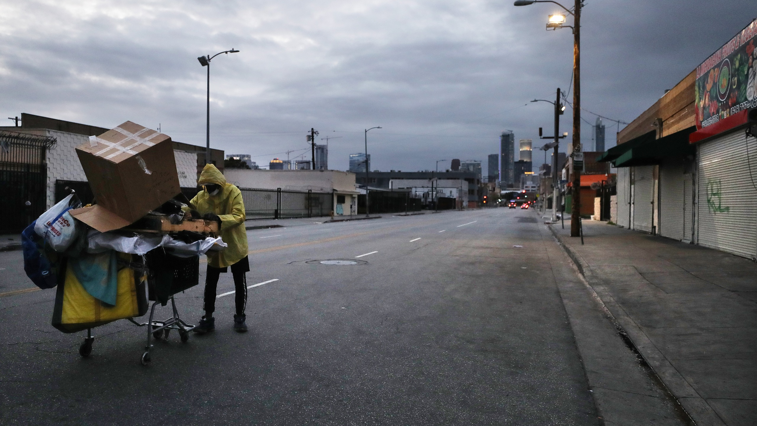 A man who is originally from Texas and currently homeless pushes a cart with his belongings on a downtown Los Angeles street amidst the coronavirus pandemic on April 18, 2020. (Credit: Mario Tama / Getty Images)