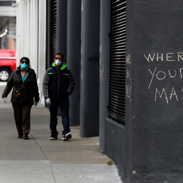 Pedestrians walk by graffiti encouraging the wearing of masks on April 20, 2020, in San Francisco, California. (Justin Sullivan/Getty Images)