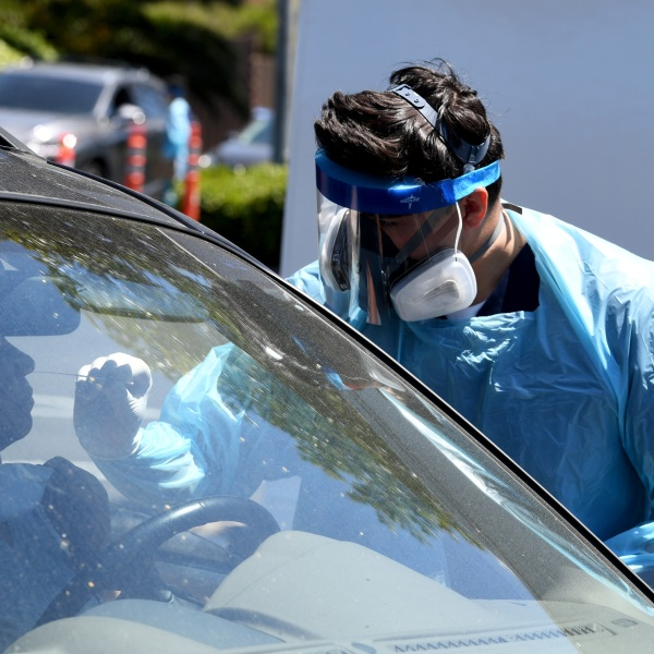 Workers wearing personal protective equipment (PPE) perform drive-up COVID-19 testing administered from a car at Mend Urgent Care testing site for the novel coronavirus at the Westfield Culver City on April 24, 2020 in the Culver City neighborhood of Los Angeles. (Kevin Winter/Getty Images)