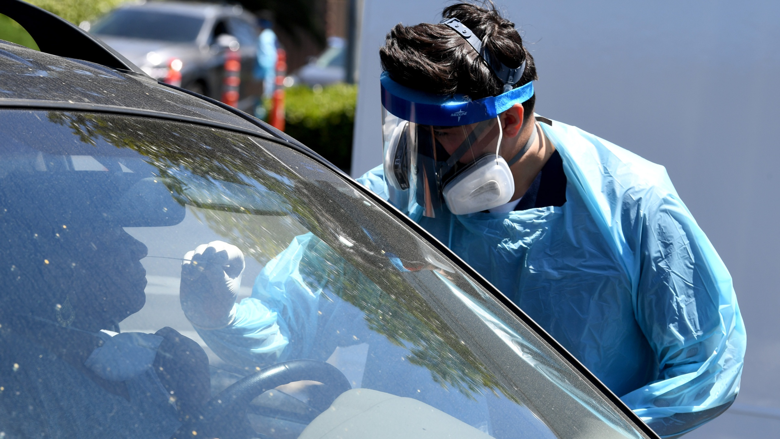 Workers wearing personal protective equipment perform drive-up COVID-19 testing at Mend Urgent Care testing site for the novel coronavirus at the Westfield Culver City on April 24, 2020, in Culver City. A nasopharyngeal swab test kit is used at this COVID-19 testing center to determine the viral load and virus count of a patient. (Kevin Winter / Getty Images)