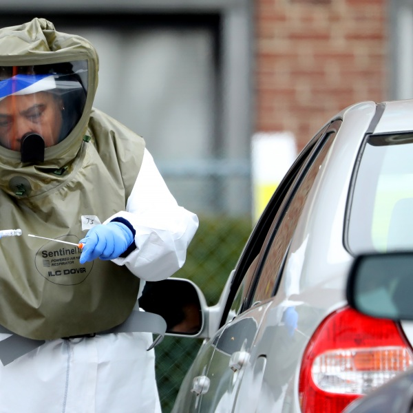 A medical professional administers a coronavirus test at a drive-thru testing site at Cambridge Health Alliance Somerville Hospital on April 28, 2020 in Somerville, Massachusetts. (Maddie Meyer/Getty Images)