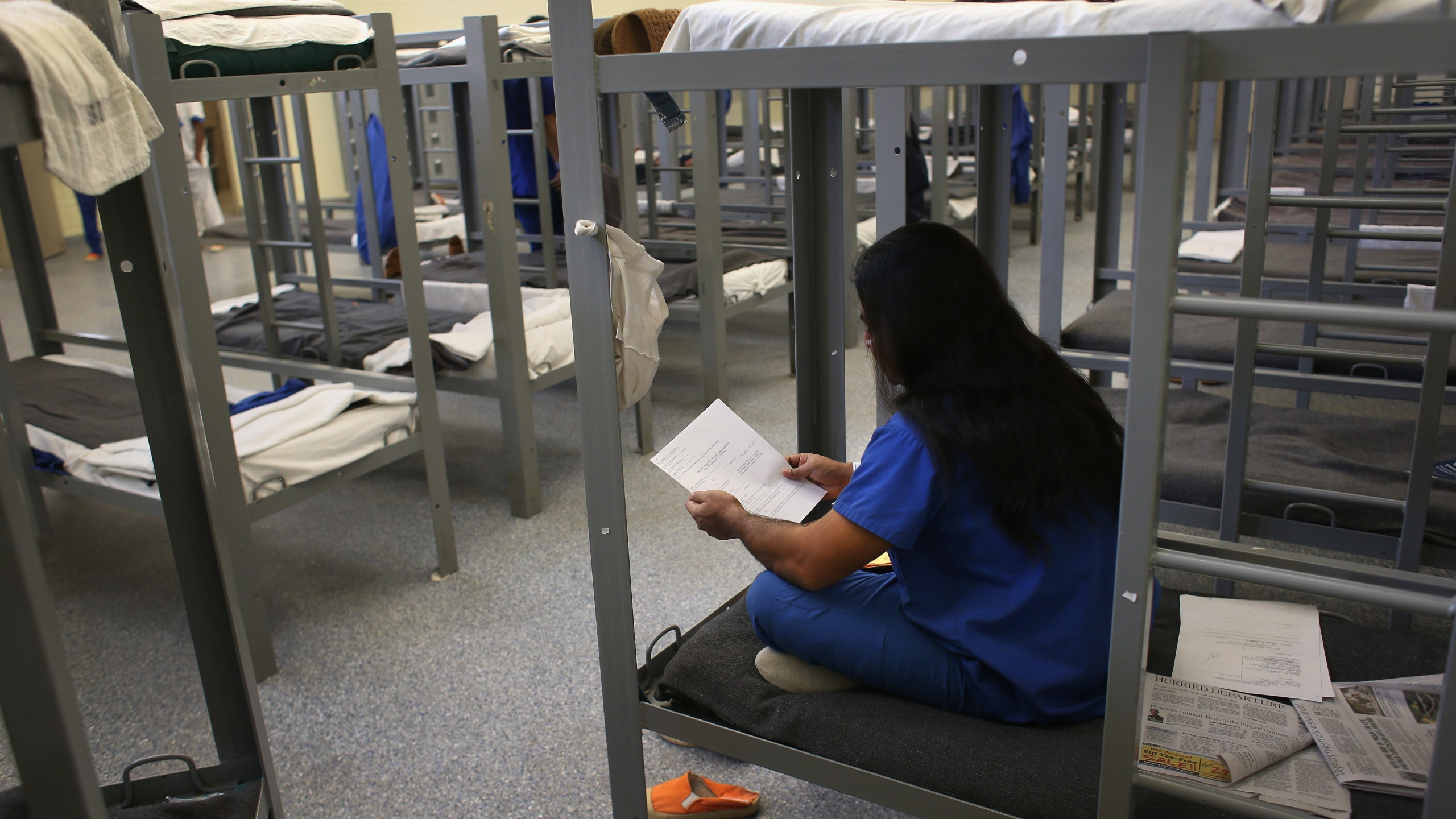 An immigration detainee from Bangladesh reads through his case papers while on his bunk at the Immigration and Customs Enforcement (ICE), detention facility on February 28, 2013 in Florence, Arizona. (John Moore/Getty Images)