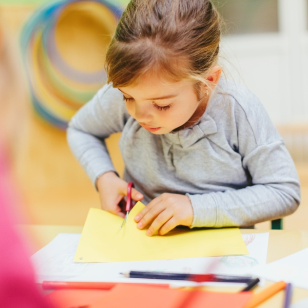 A preschooler cuts colored paper with scissors in this file photo. (Getty Images)